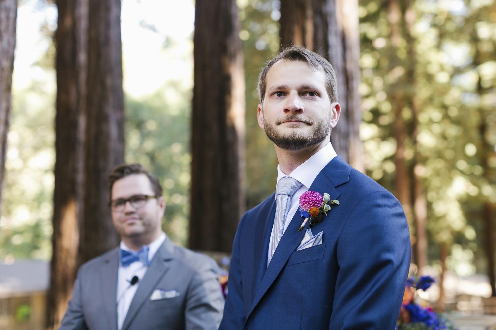 Groom in blue suit awaits his bride in the redwoods