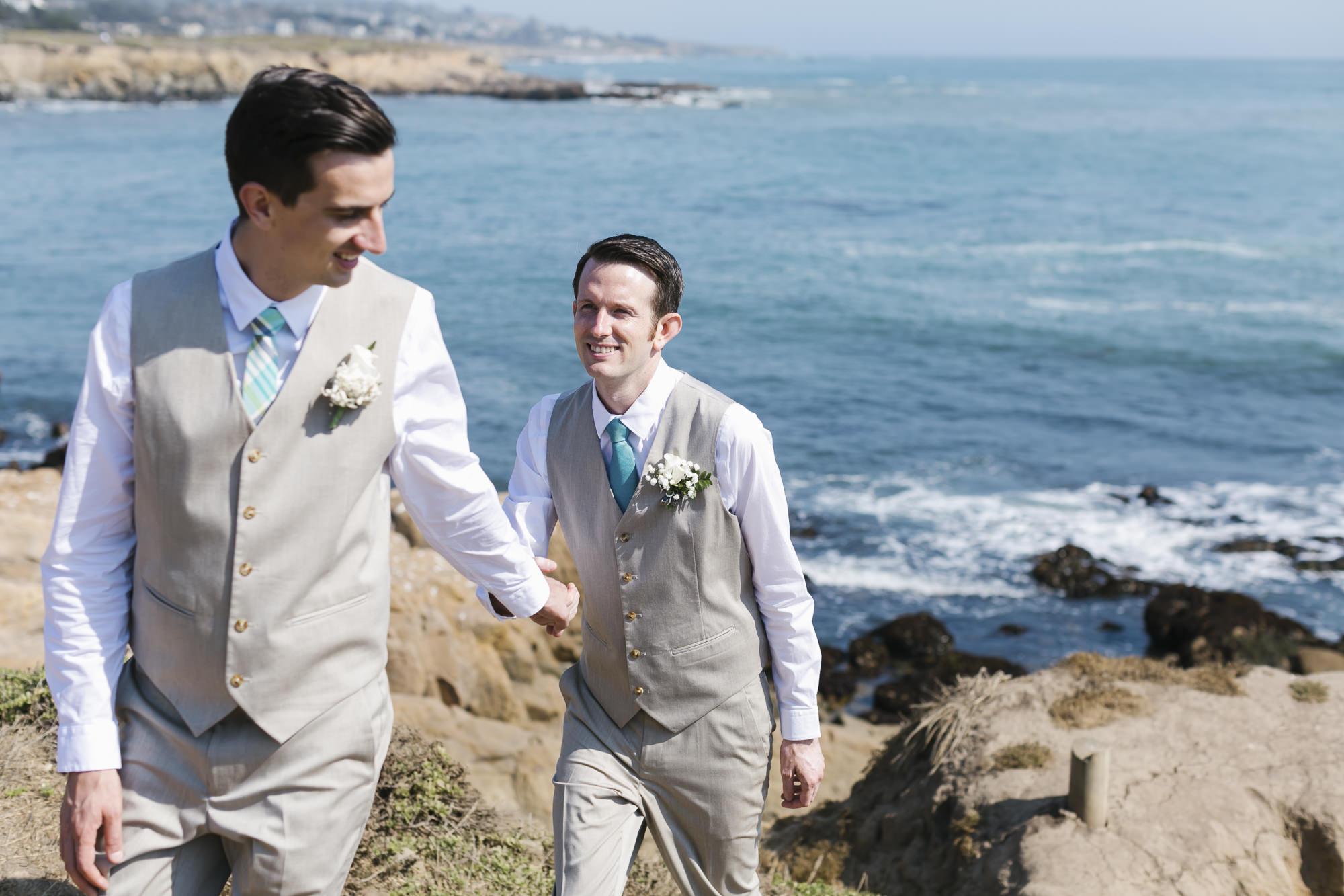 Same sex wedding couple walk together along the coast of Cambria