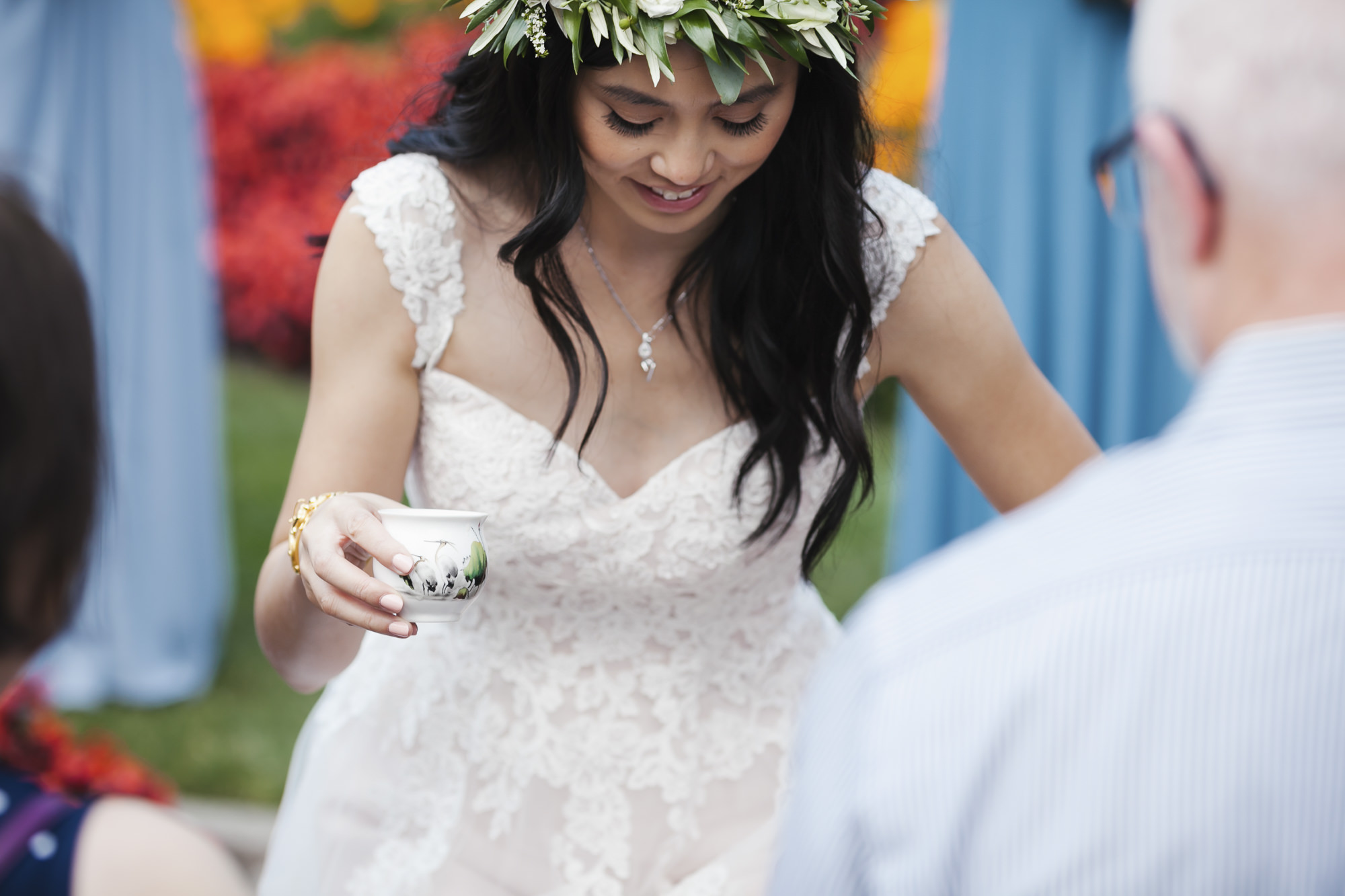 Bride with leaf crown kneels for tea ceremony