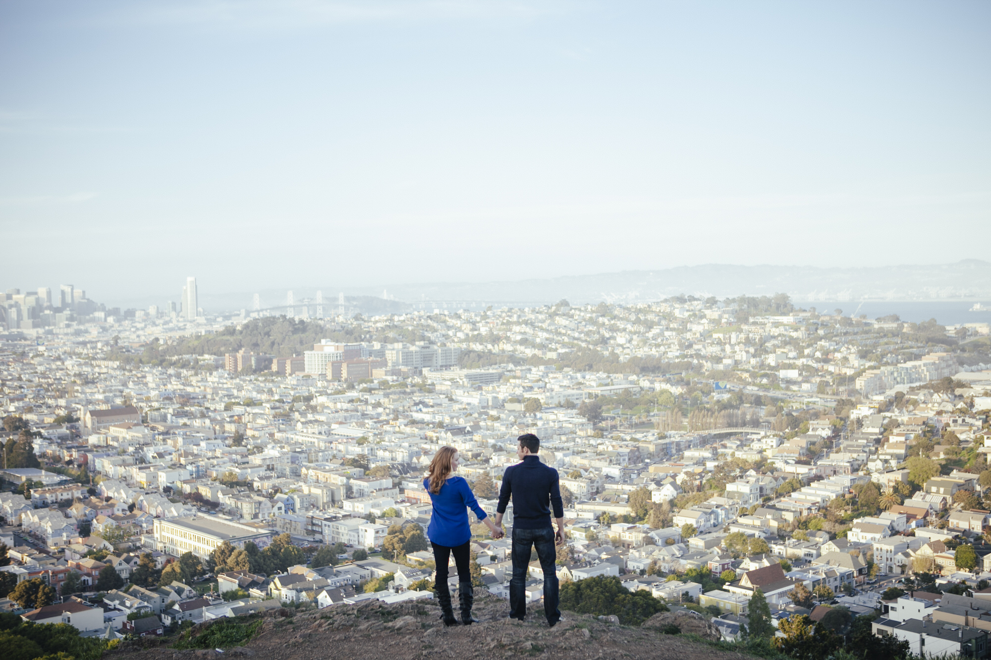 Couple stand in front of the view of San Francisco atop Bernal Heights Park during their engagement portraits.