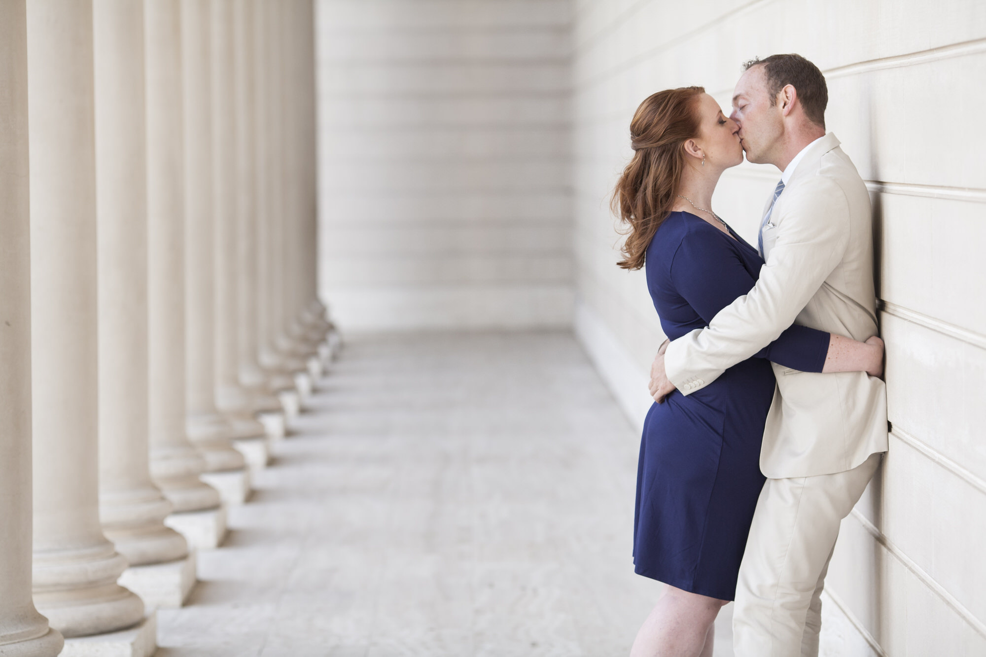 Couple kiss among the columns at the Legion of Honor during their engagement portraits.