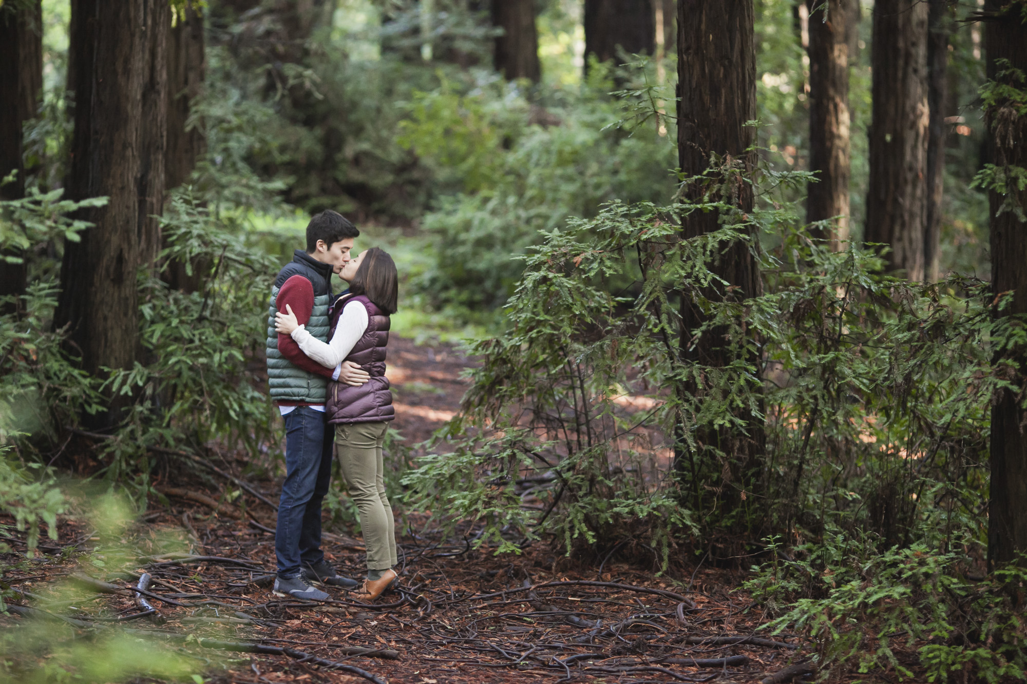 Outdoorsy couple kiss during their engagement portraits at Oakland Redwood Regional Park