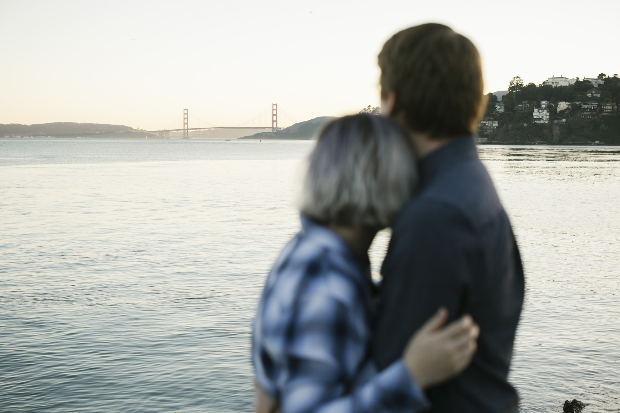 Engagement portraits in Tiburon with Golden Gate Bridge in distance at sunset