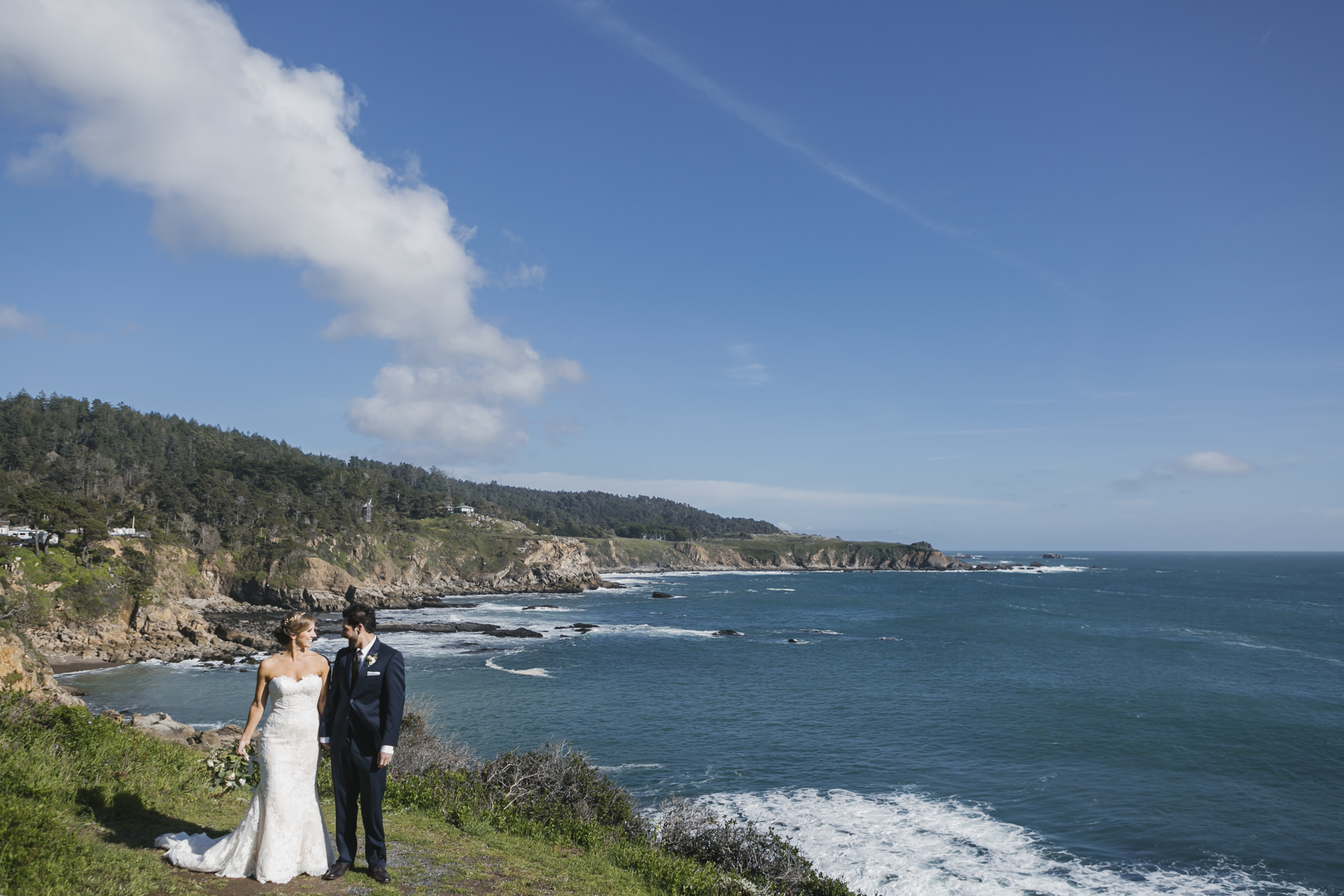 Wedding couple walk along the coast at Timber Cove Resort