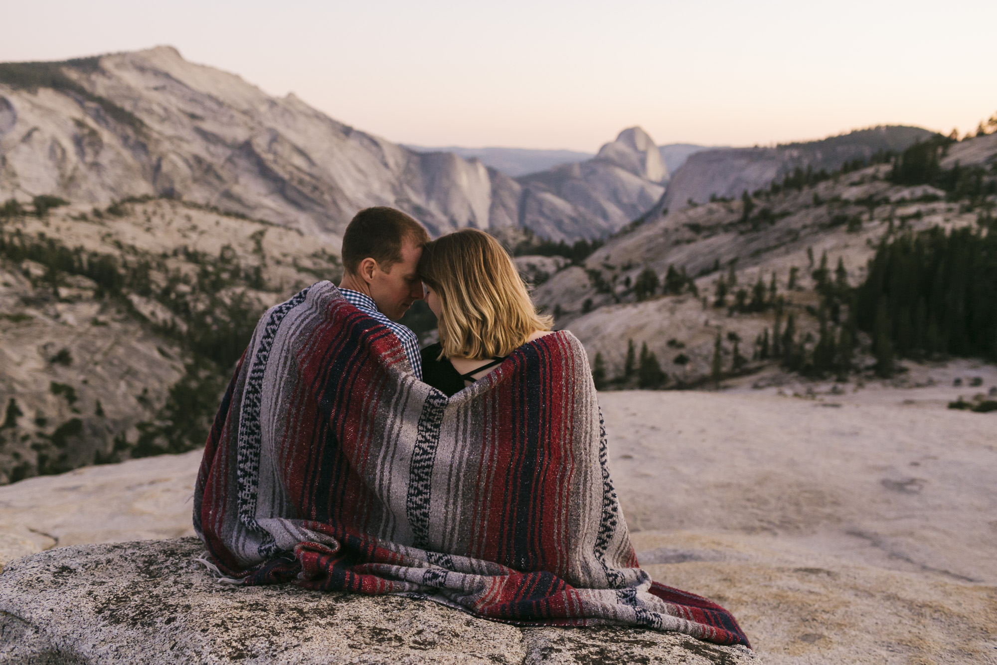Couple snuggle together at sunset wrapped in a blanket in Yosemite with a view