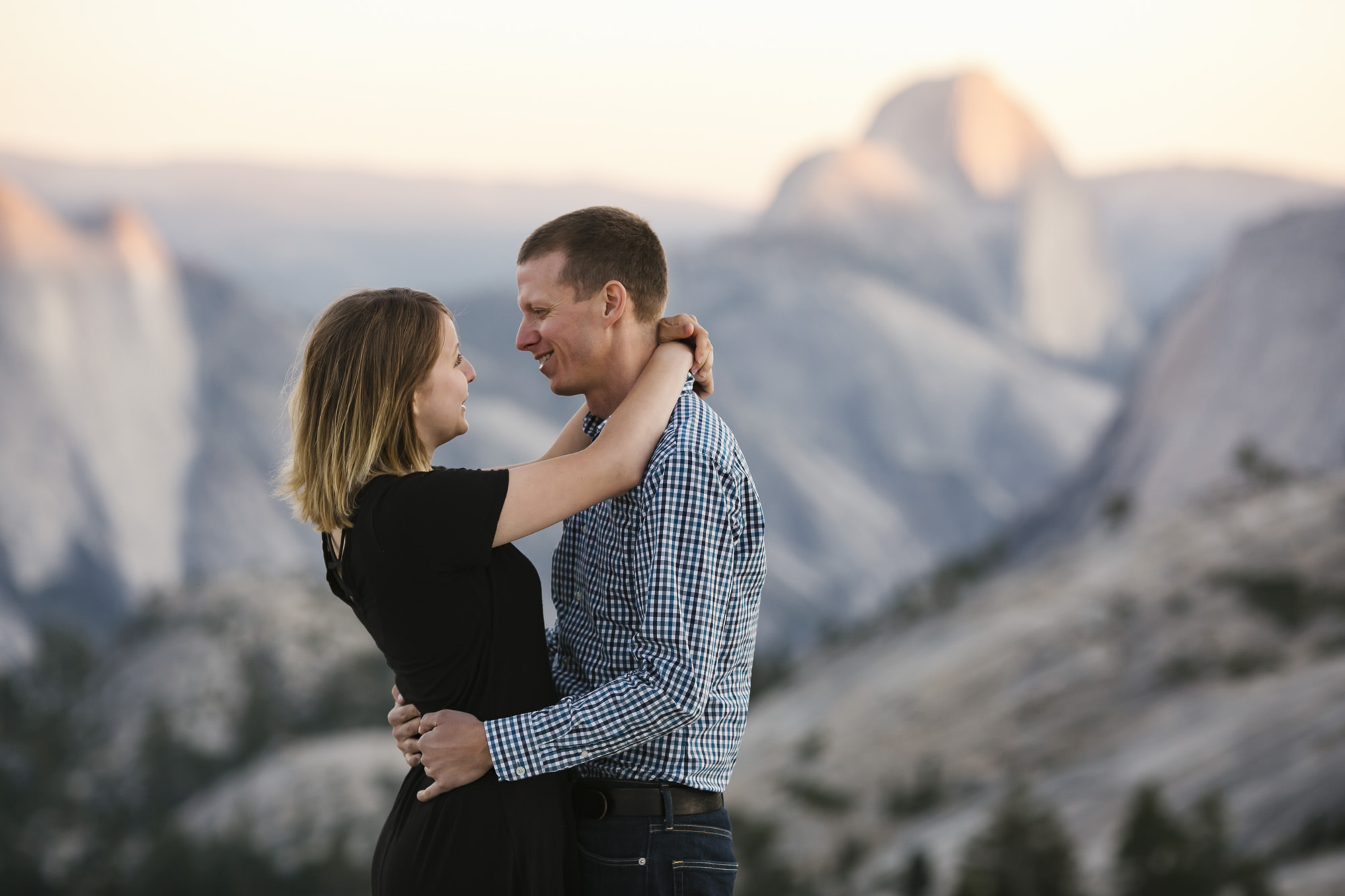 Couple hug in Yosemite at sunset with Half Dome in the background