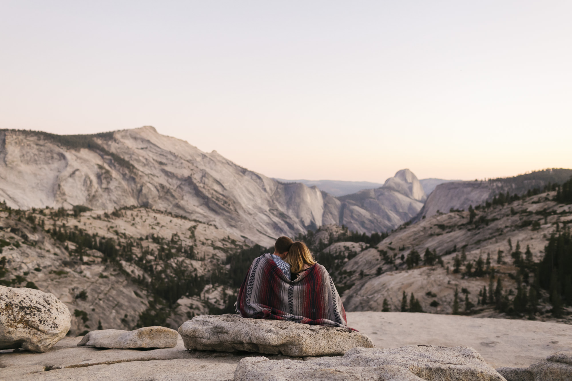 Couple snuggle with blanket in Yosemite at sunset