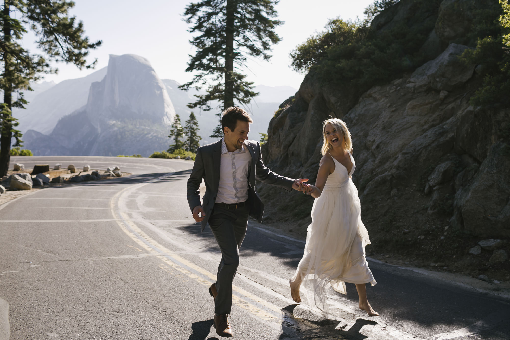 Wedding couple run down the road at Glacier Point in Yosemite