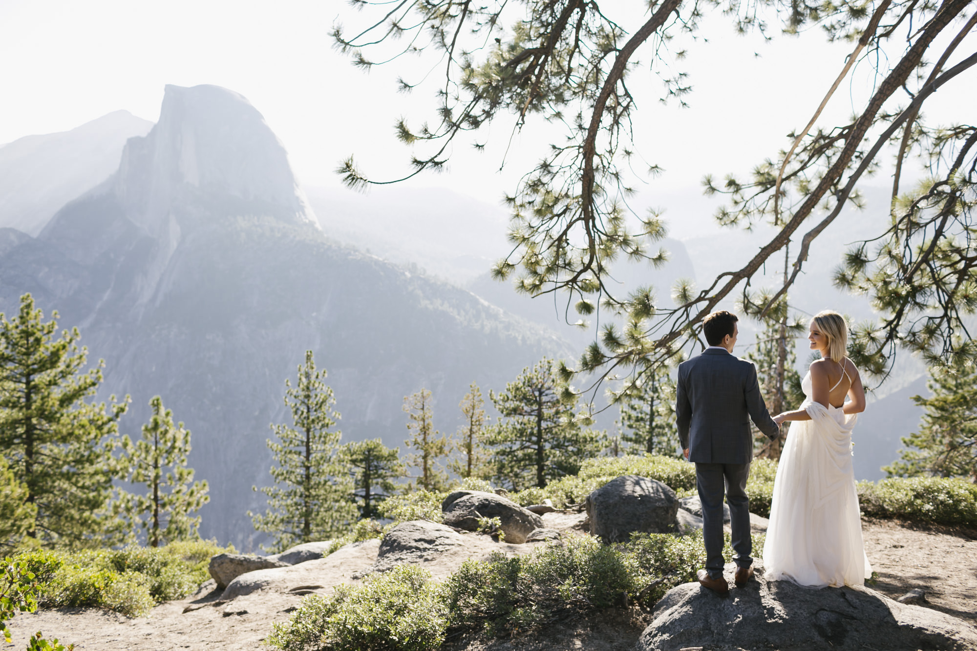 Wedding couple enjoy the view of Half Dome at Glacier Point in Yosemite