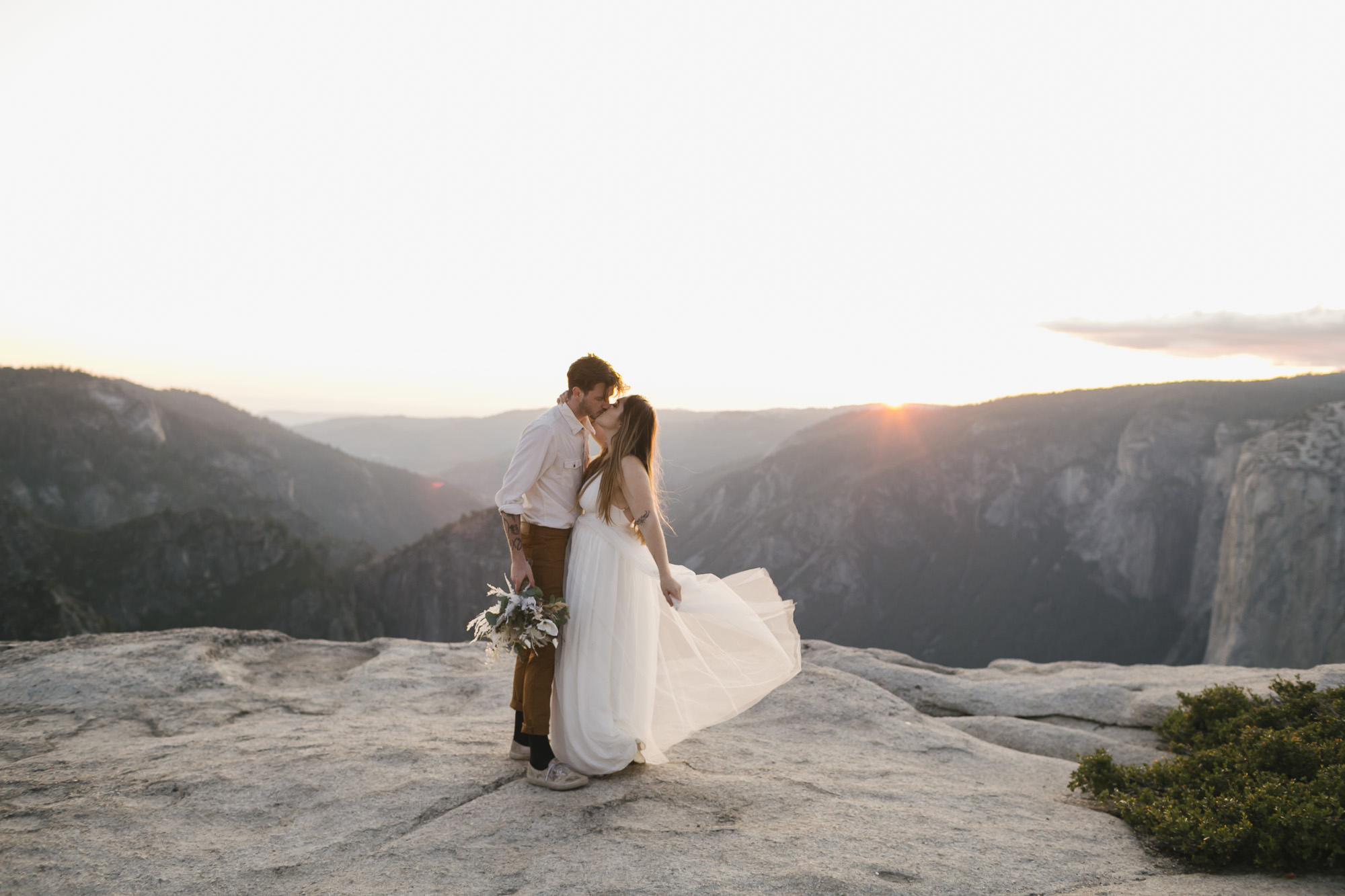 Bride and groom kiss at sunset at Taft Point in Yosemite