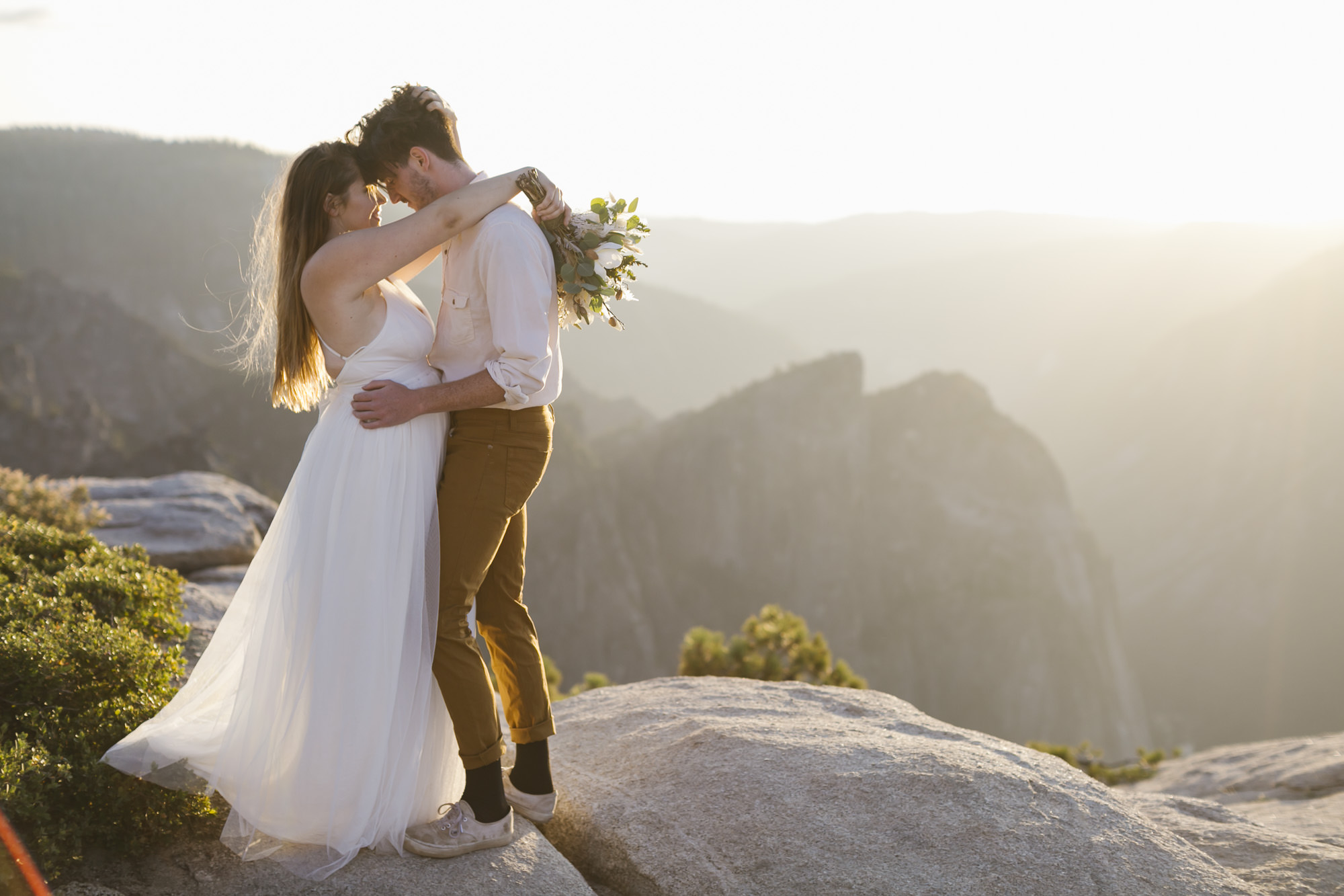 Bride and groom hug after eloping at Taft Point in Yosemite