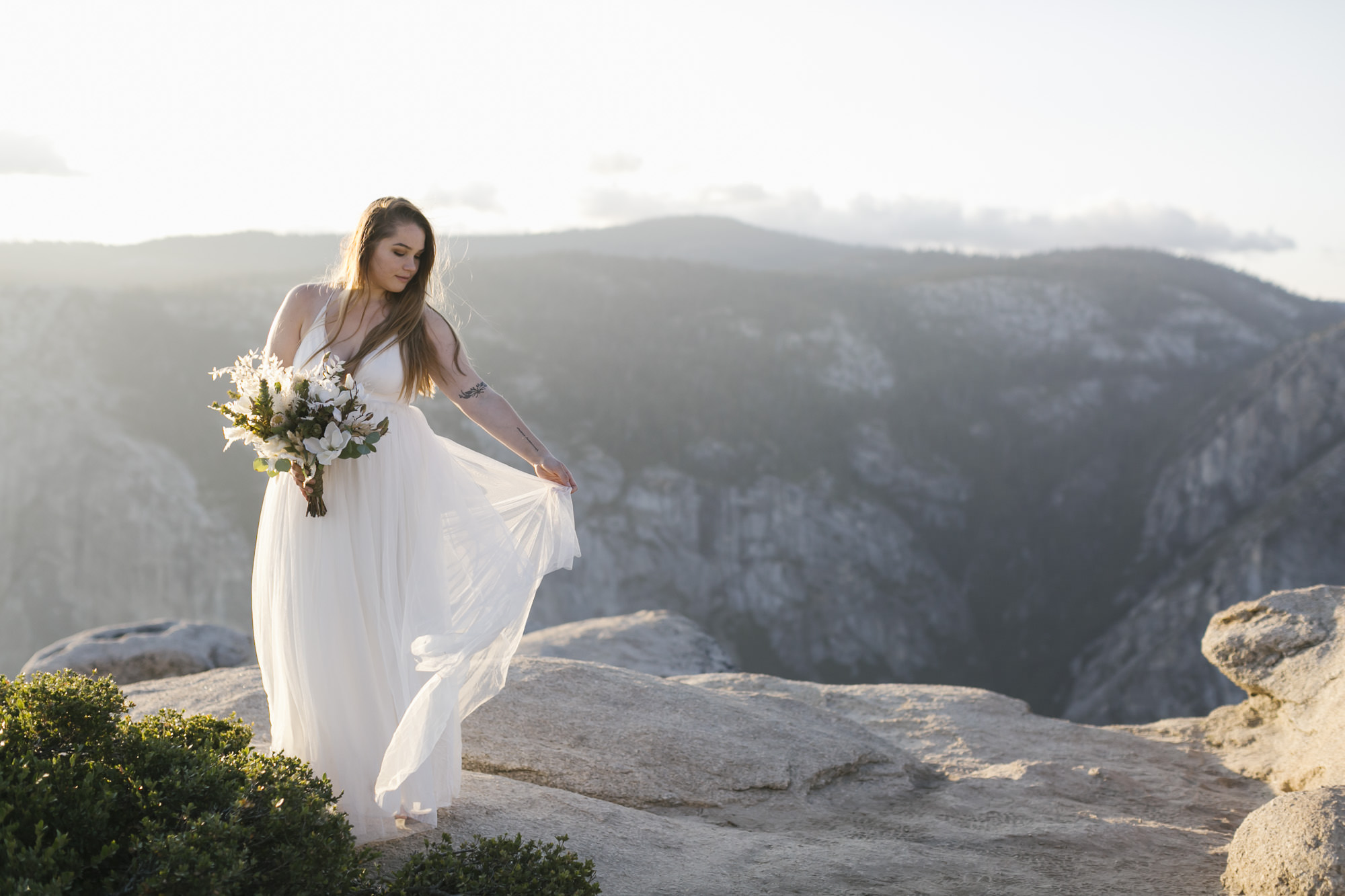 Bride plays with her wedding dress at Taft Point