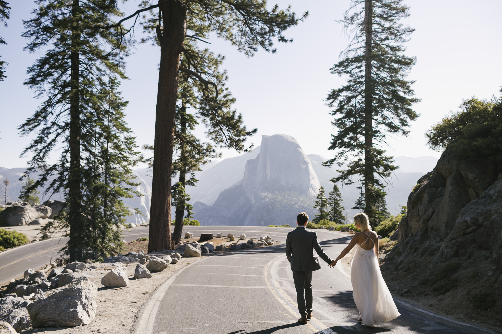 Wedding couple hold hands and walk along the road at Glacier Point