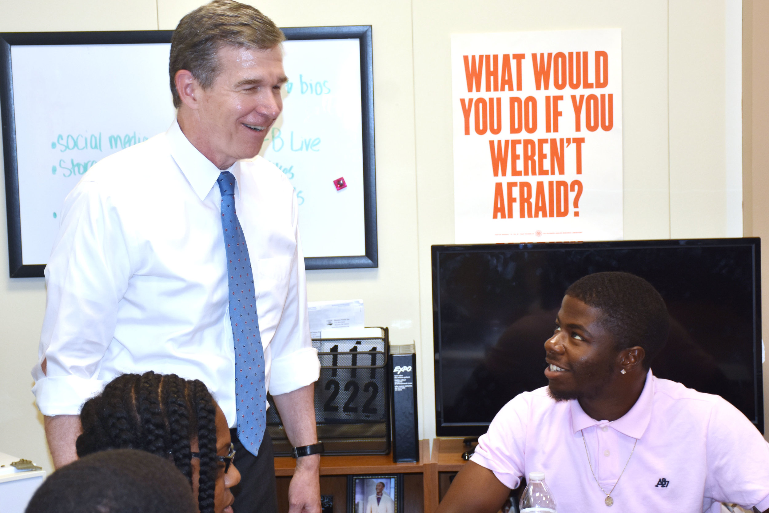 Gov. Roy Cooper and Mikel Taylor, 18, share a laugh during the governor's visit on Tuesday. Taylor is an intern for Kinston Teens this summer. Photo by Bryan Hanks / Neuse News