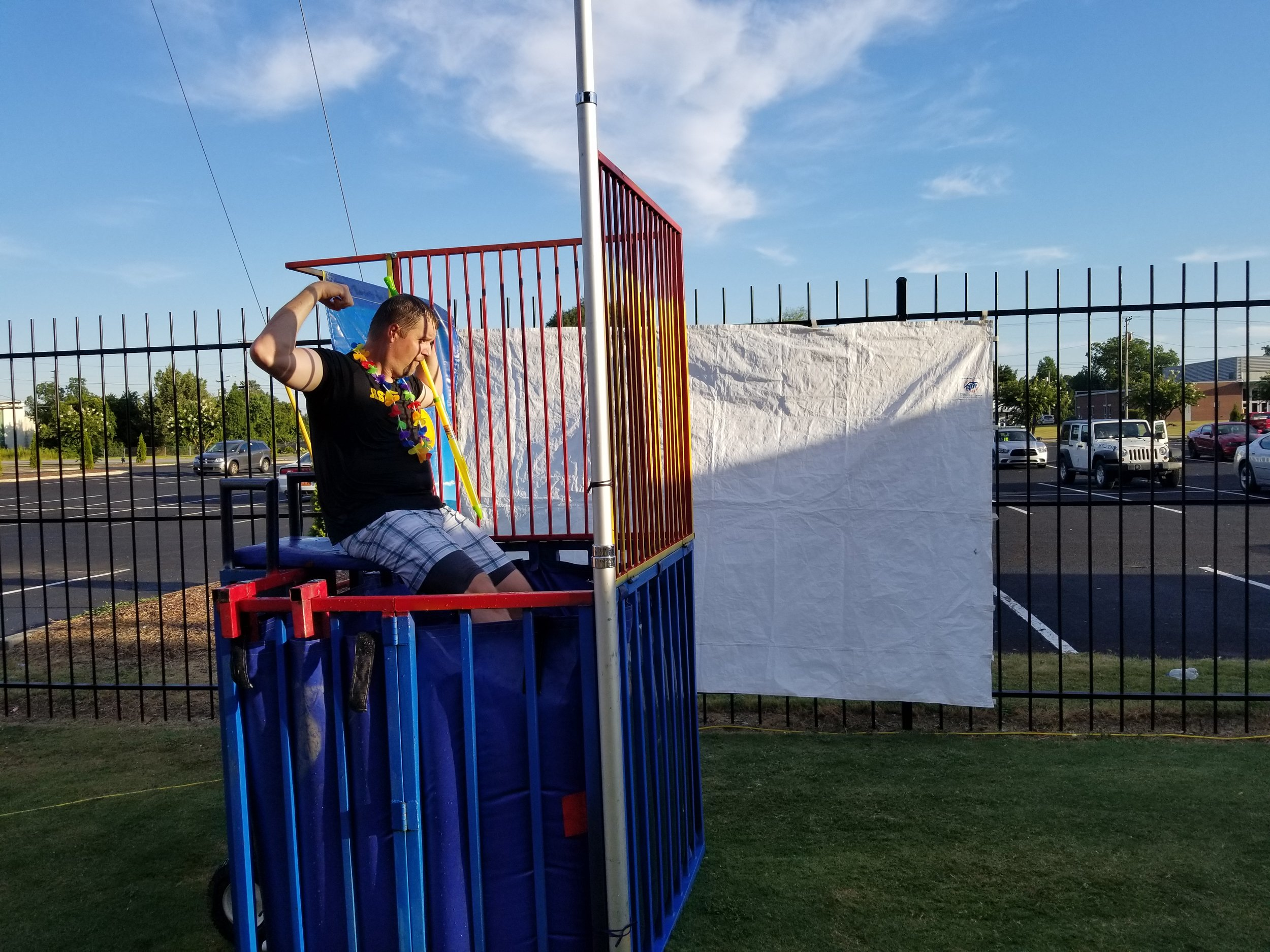 Kinston City Manager Tony Sears flexes his muscles as a taunt to the dunk booth thrower during the 2017 National Night Out. Submitted photo.