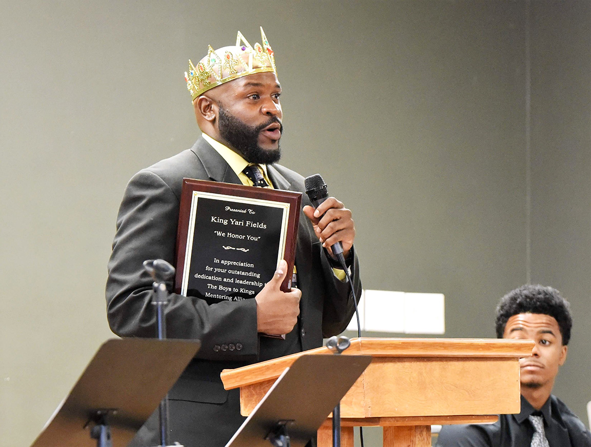 Boys to Kings Mentoring Alliance Director Kenyari Fields speaks at Saturday's event while holding a plaque presented to him by parents of some of the students. Photo by William 'Bud' Hardy / Neuse News