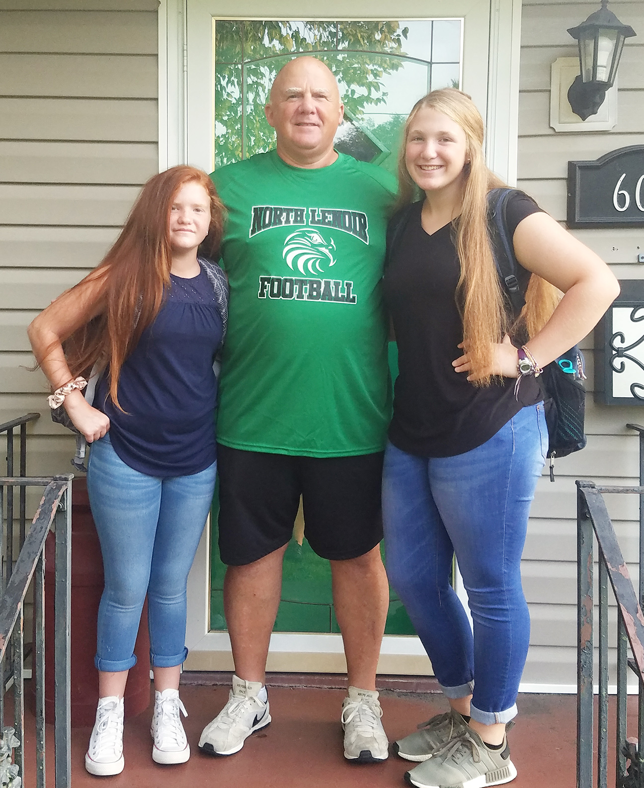 Faith Collins, left, eighth grade, Frink Middle School and Lark Collins, junior, North Lenoir High School pose with their father, Jim Collins, the first-year North Lenoir head football coach.