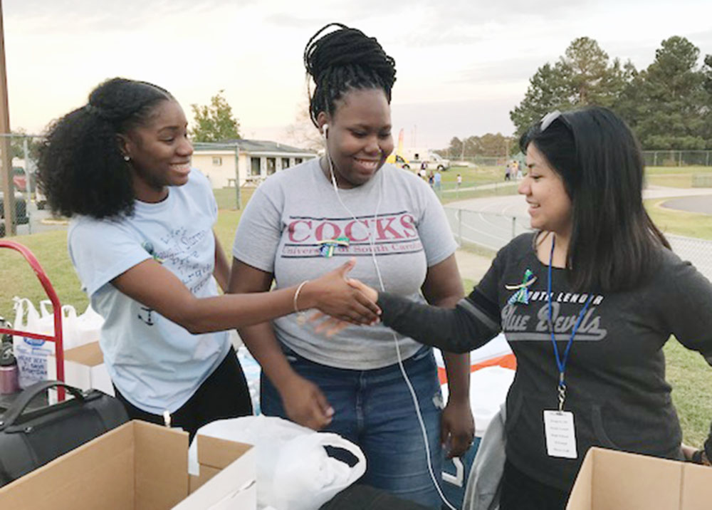 Kinston High students Leslie Sutton, left, and Andrea King work with South Lenoir student Josi Esquivel to collect donations for Jones County students during a Kinston-South Lenoir football game earlier this month.