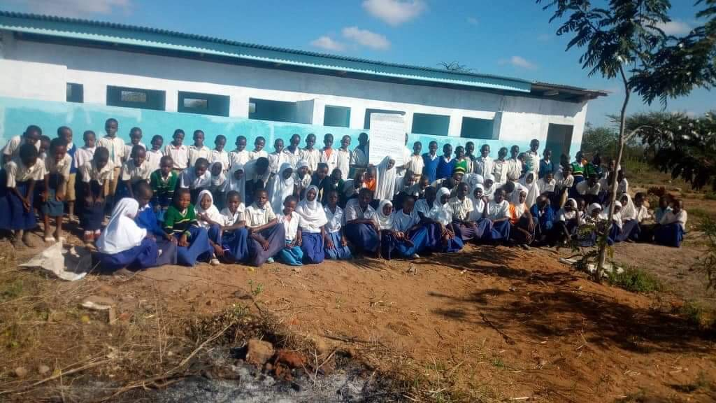 Pictured are members of the Toloha primary school in front of the school toilet and washroom facility in Tanzania.