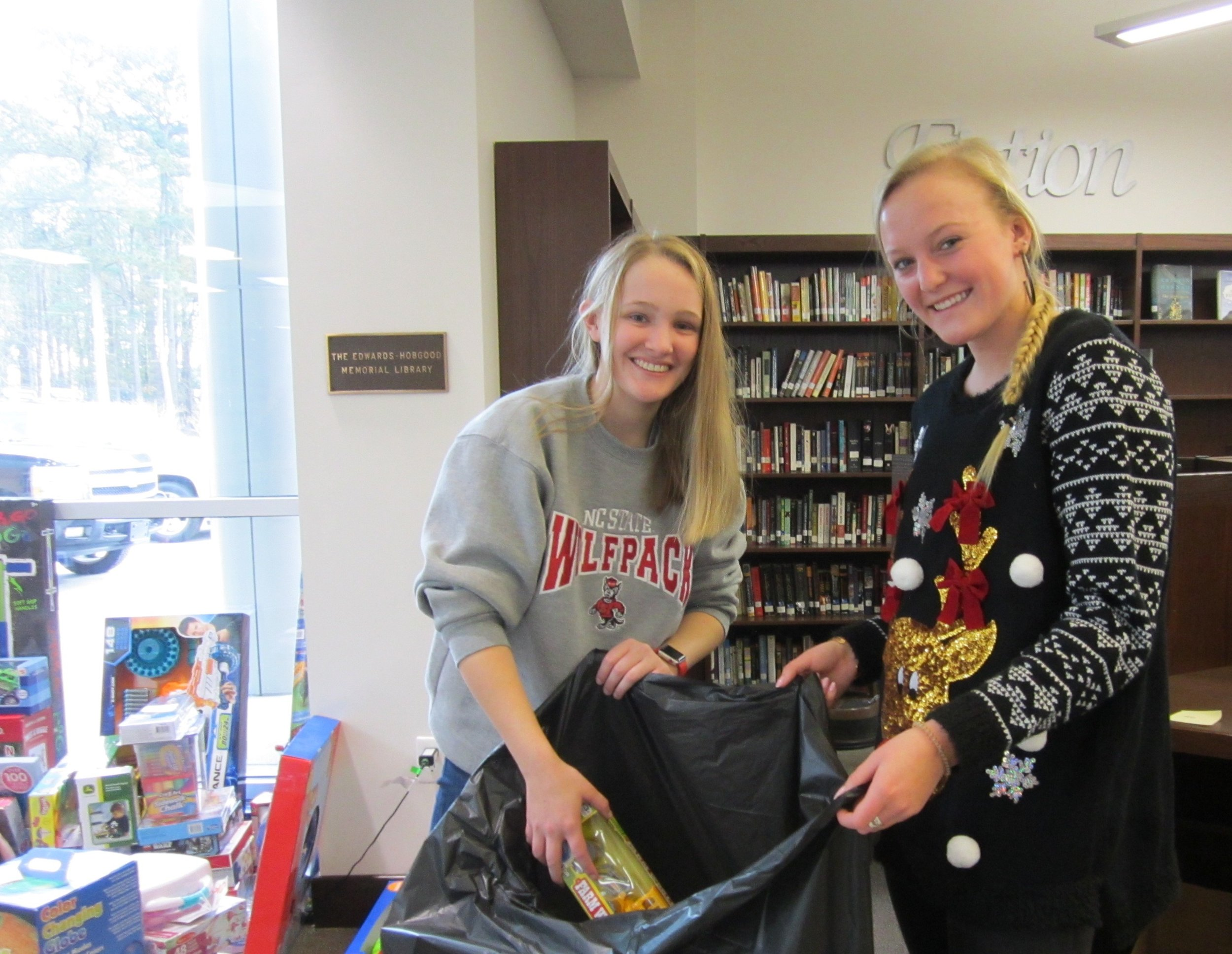 Reagan Perry and Megan Blair help load toys donated by Parrott students for the Salvation Army Christmas Cheer Giveaway.