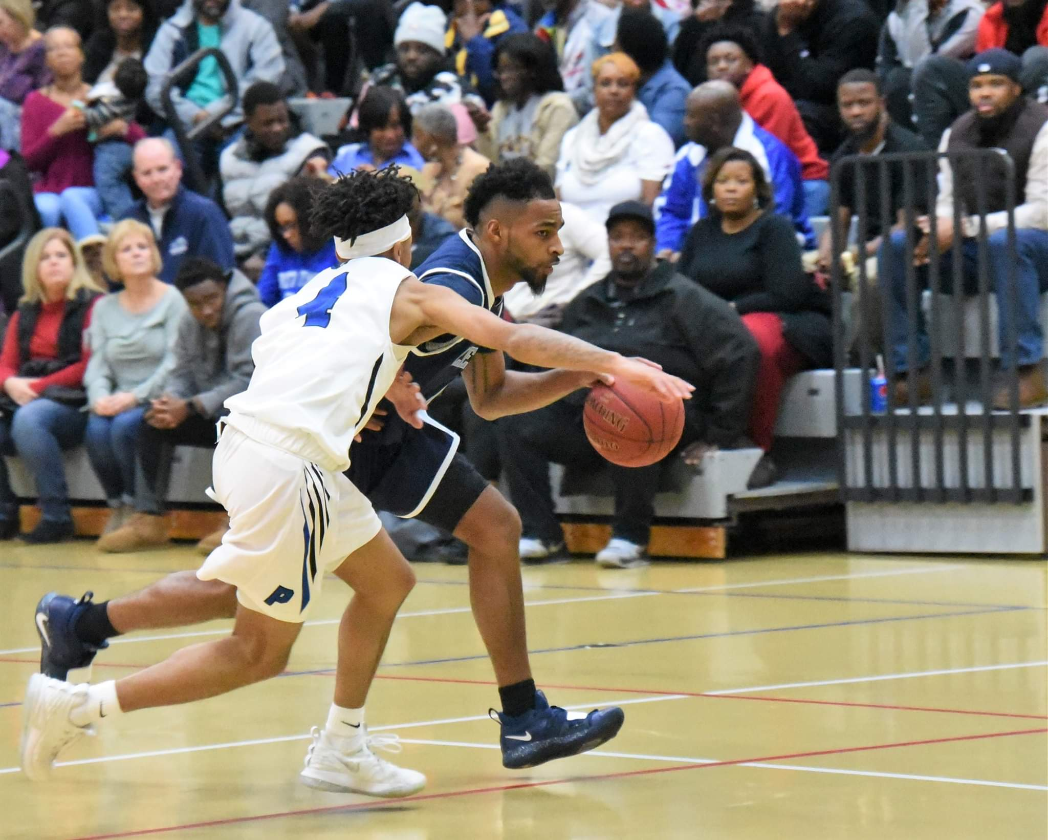"""Lenoir Community College's Darius Dunn brings the ball up the court under duress from Pitt Community College's DonQuez Davis in Wednesday's game. Photo by William """"Bud"""" Hardy / Neuse News"""