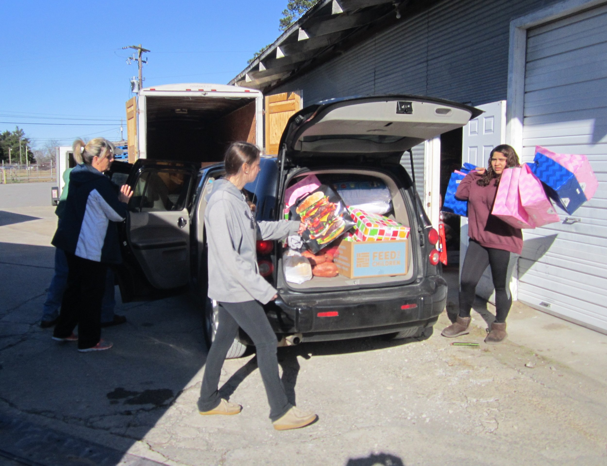 Volunteers help load cars with bags of Christmas gifts and donated groceries. Photo by Vicki Kennedy.