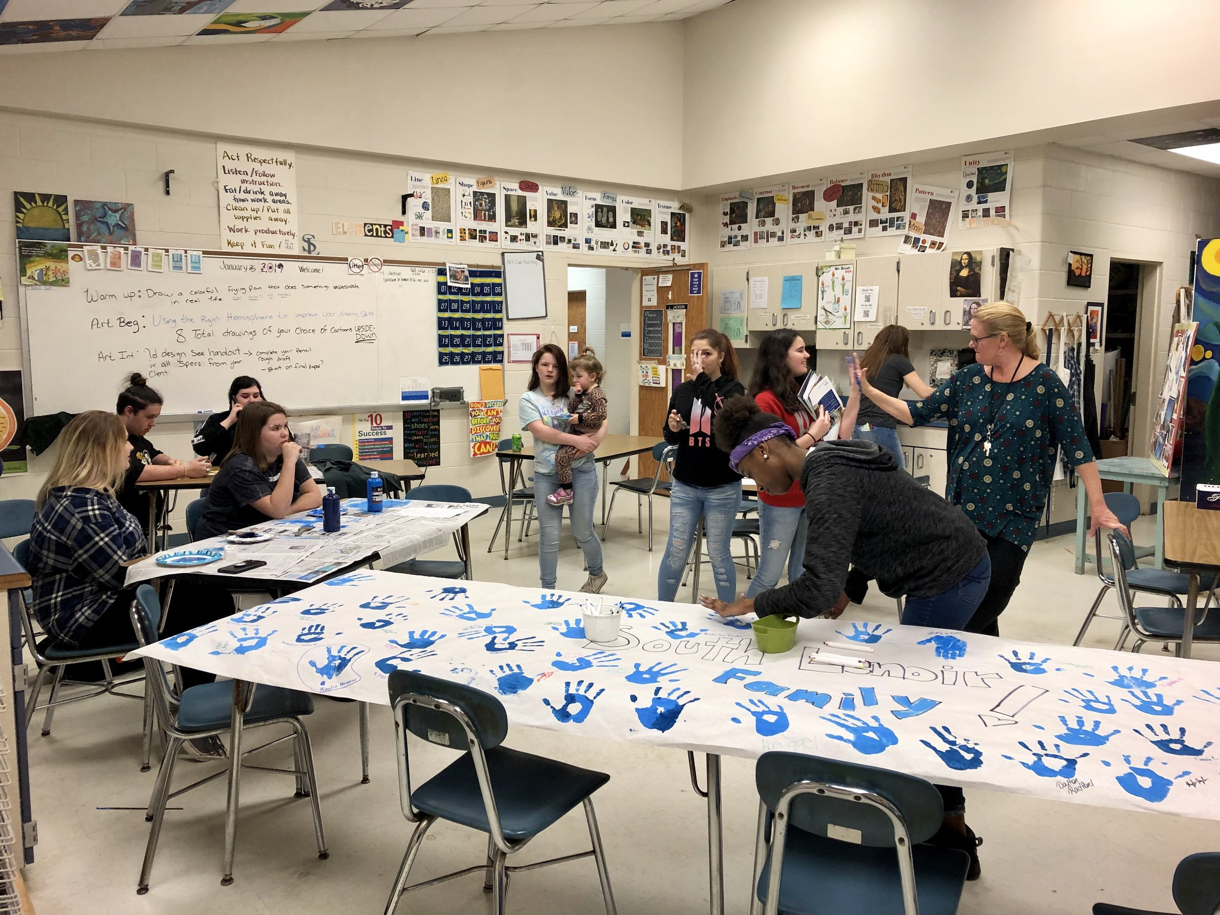 Art teacher Laura Jackson helps students and families create a banner.  Photo by Catherine Hardee / Neuse News