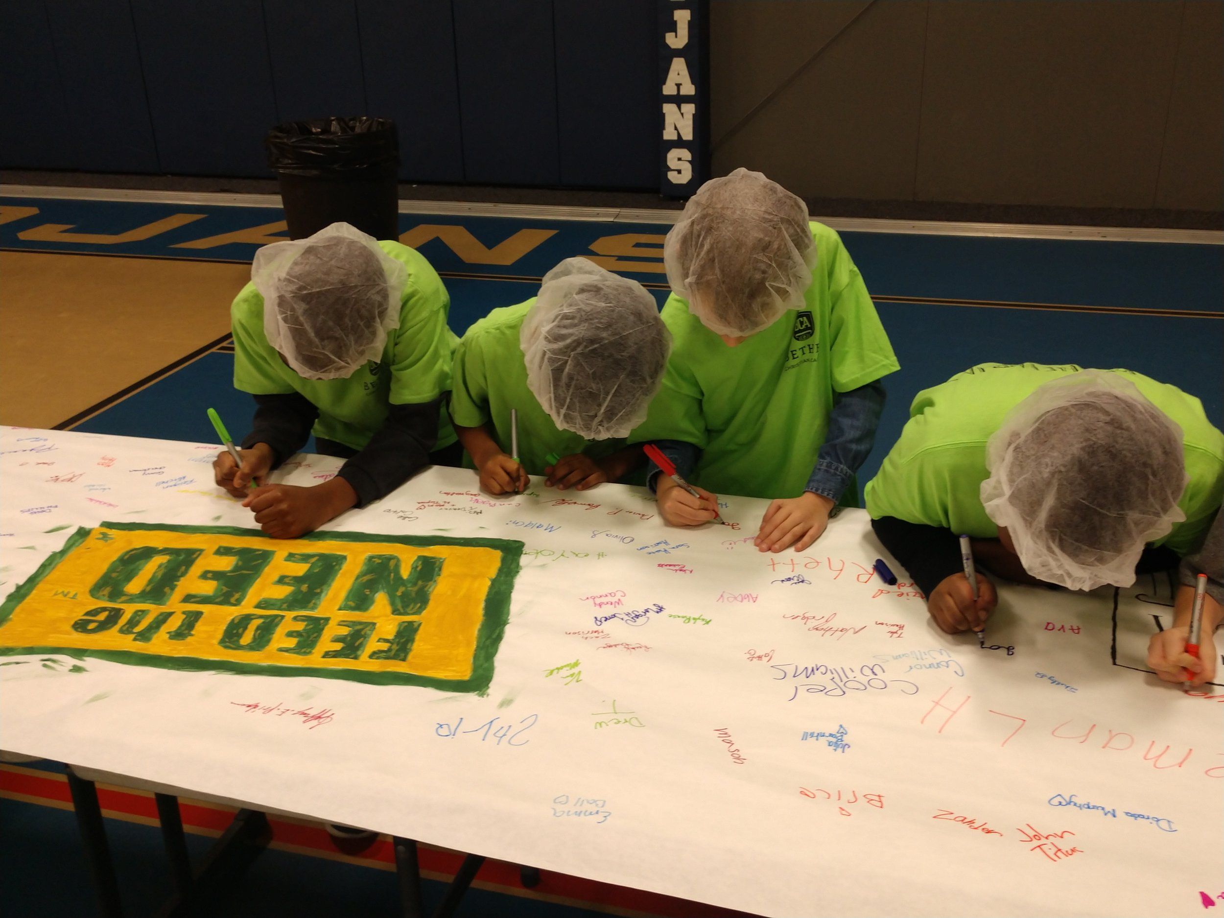 Second-graders at Bethel Christian Academy sign the 'Feed The Need' banner Tuesday at the school's gym. The school packaged about 10,000 meals to ship to Haiti. Photo by Junious Smith III / Neuse News
