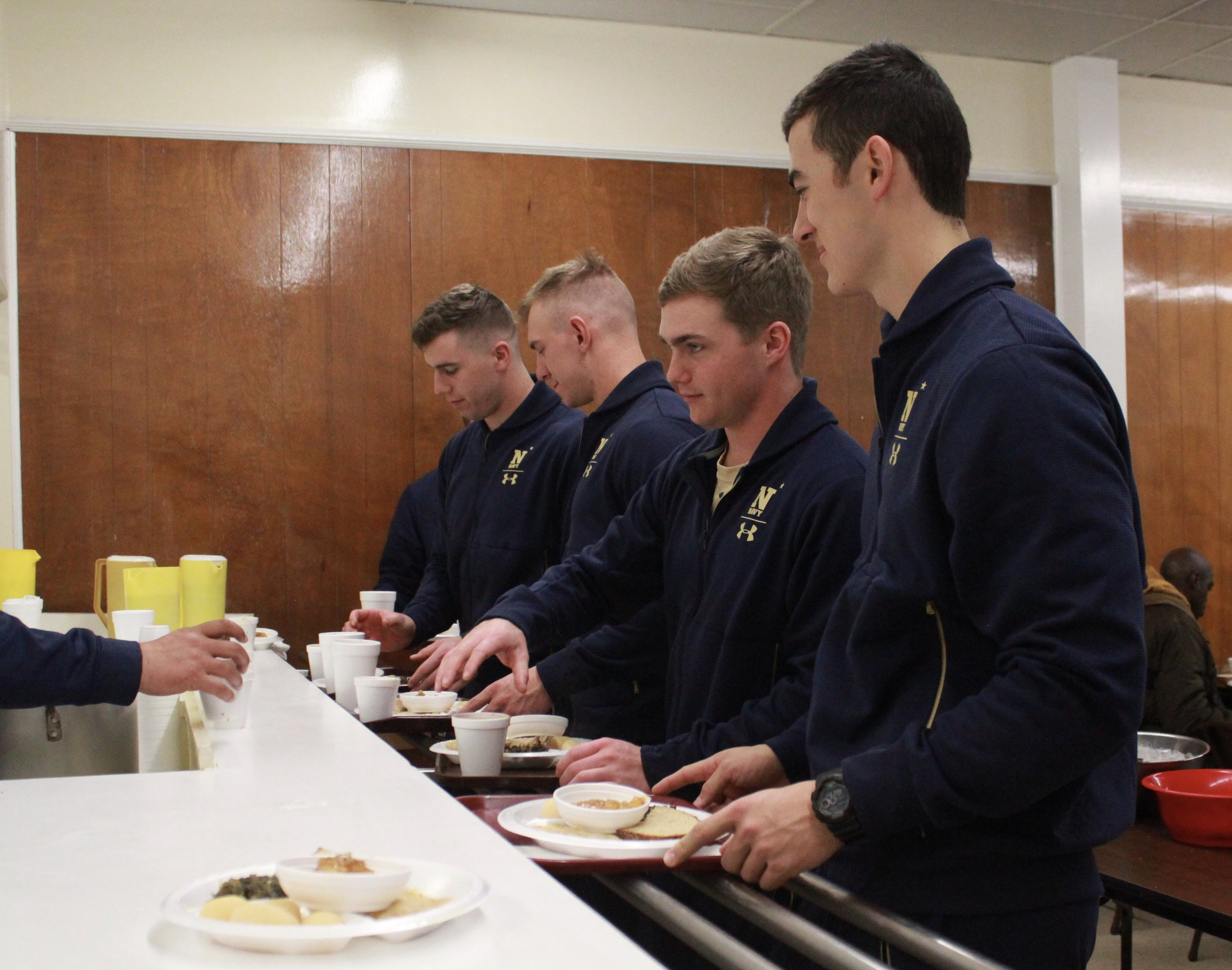 From left, U.S. Naval Academy baseball players Charlie Connolly, Evan Lowery, Jack Ferguson and Noah Song serve meals at Mary's Kitchen in Kinston on Friday. Photo by Linda Whittington / Neuse News