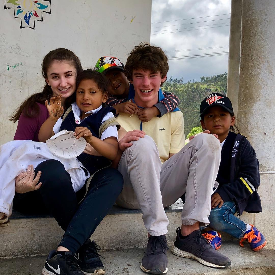Aliza Matthews, left, and Jenks Jenkins share time with some Ecuadoran children. Submitted photo