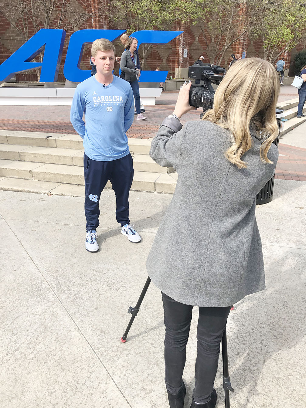 UNC men's basketball manager Tyson Creech prepares to be interviewed by WCTI ABC-12's Ariel Epstein outside the Spectrum Center in downtown Charlotte. Photo by Bryan Hanks / Neuse News