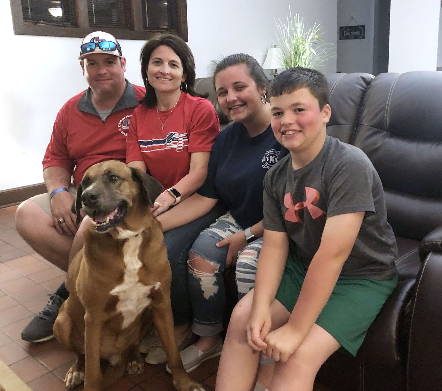Lenoir County Sheriff's Office Maj. Ryan Dawson, left, poses with his family at their home Sunday night. They are, from left, his wife Beverly Dawson, their daughter Riley, 18, and son Ashton, 11, along with their beloved Clifford. Photo by Bryan Hanks / Neuse News