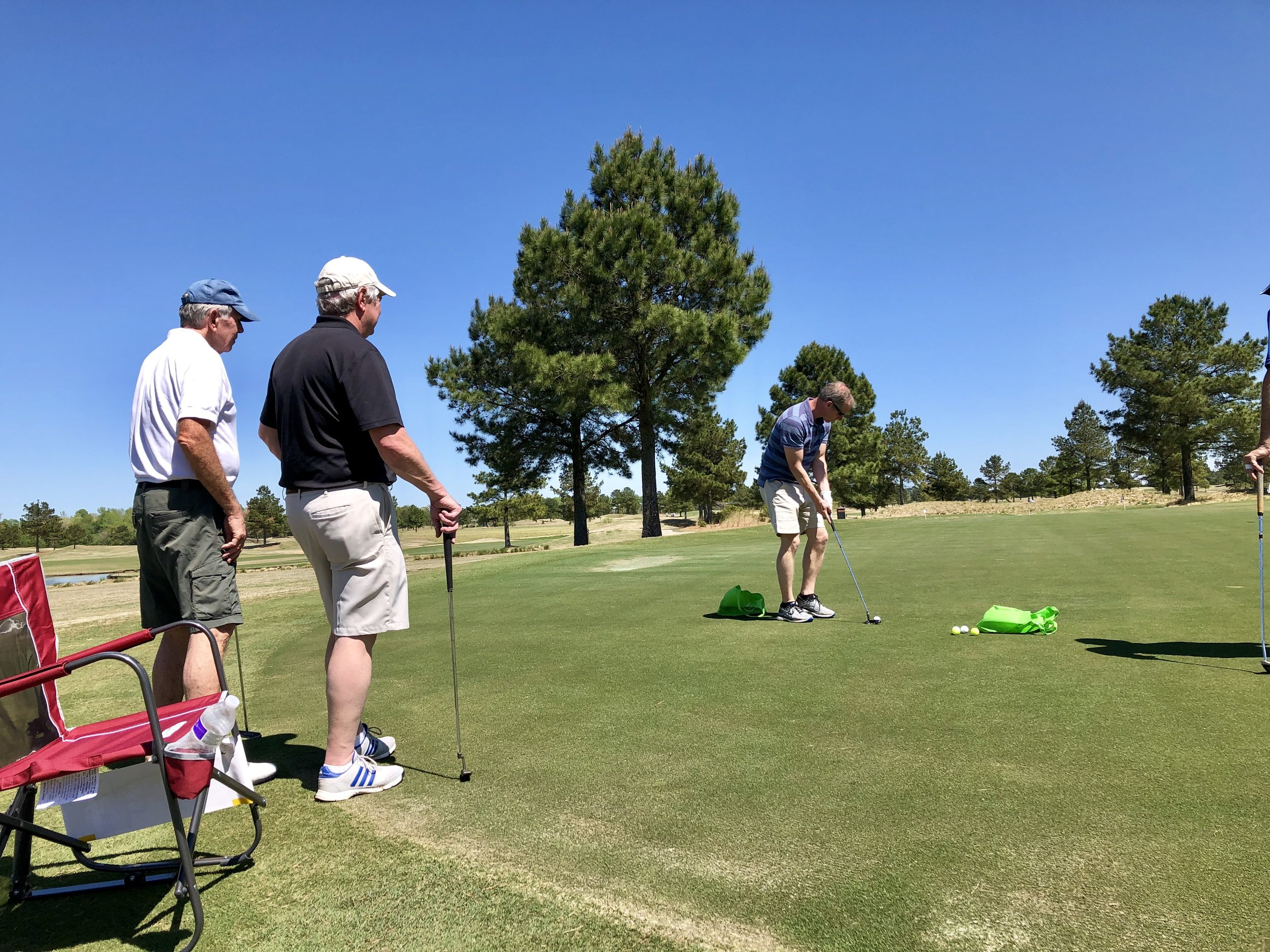 Jason McKnight lines up his putt in the putting contest during the tournament. Teammates Doug Hampton, Lee Trevino and Steve Katkaveck look on. Photo by Catherine Hardee / Neuse News