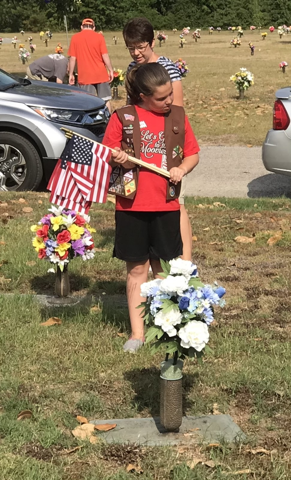 A Girl Scout member reads a cemetery marker at Pinelawn Memorial Park.