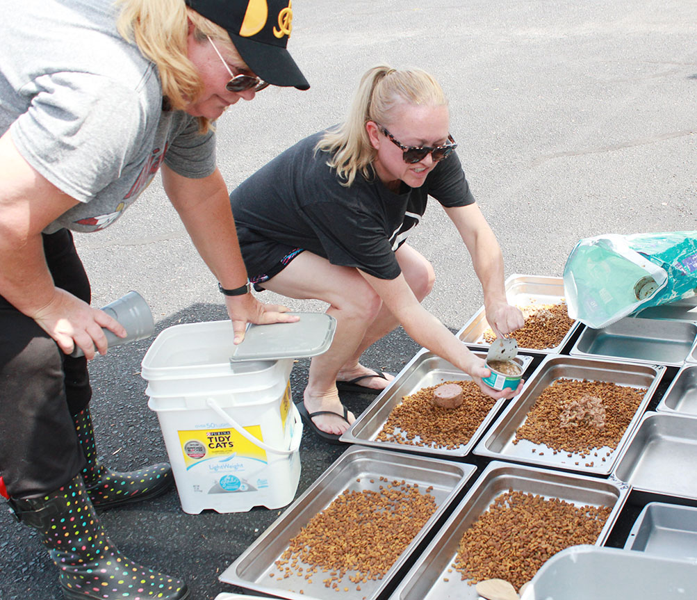 Lori Cahoon, left, and Janell Bullock prepare the pans with dry and wet food prior to heading out to the cat colonies. Photo by Linda Whittington / Neuse News