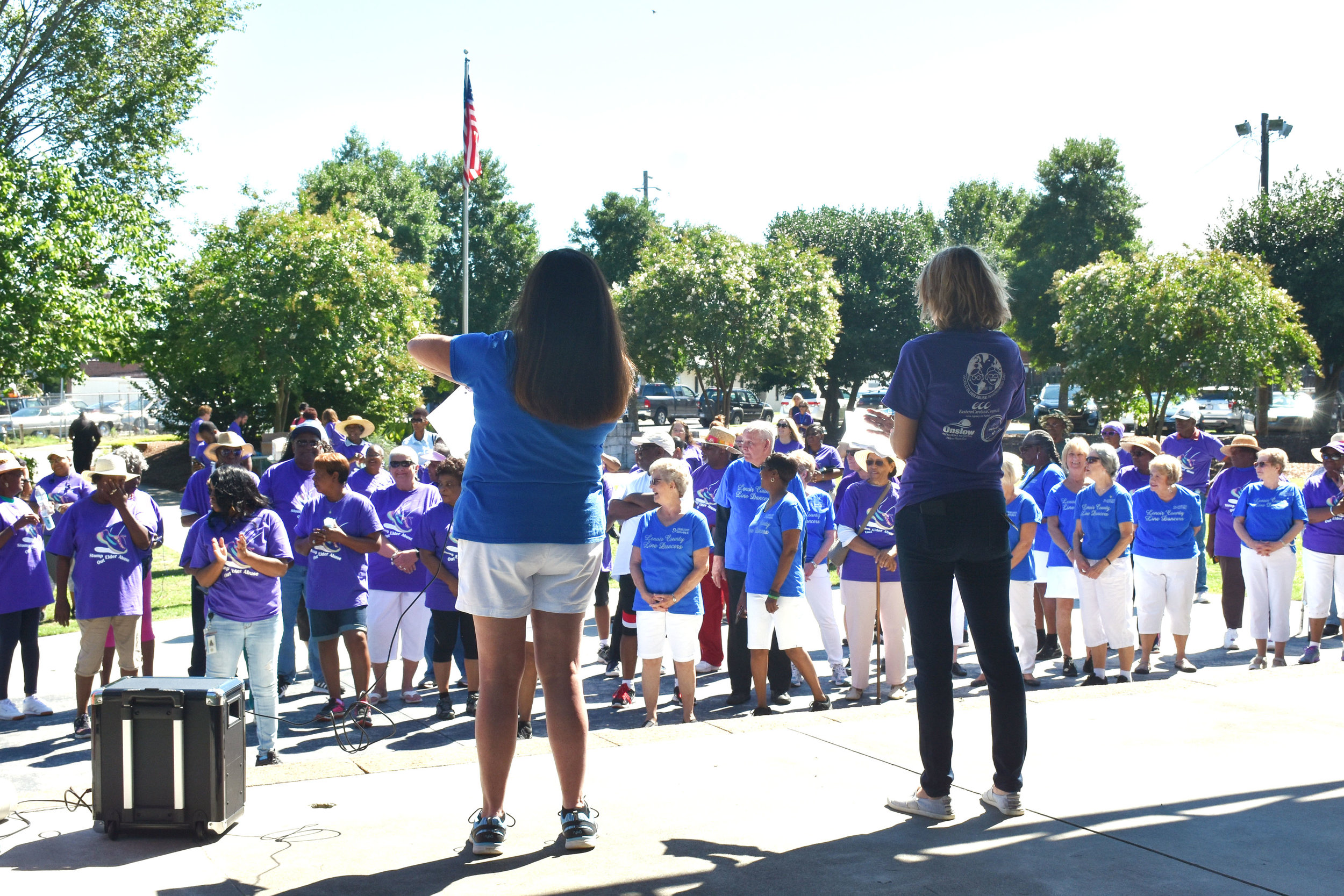 Betsy Griffin, left, and Angela Pridgen speak to the 200 residents who gathered Friday morning for the Elder Abuse Awareness Day event at Pearson Park. Photo by Bryan Hanks / Neuse News