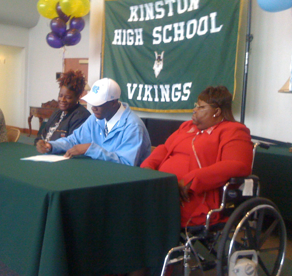 Reggie Bullock, center, signs his national letter of intent to play basketball at UNC on Nov. 12, 2009, at Kinston High School. On hand for his signing were his grandmother, Patricia Williams, right, and his mother, Danielle Long. Photo by Bryan Hanks / Neuse News