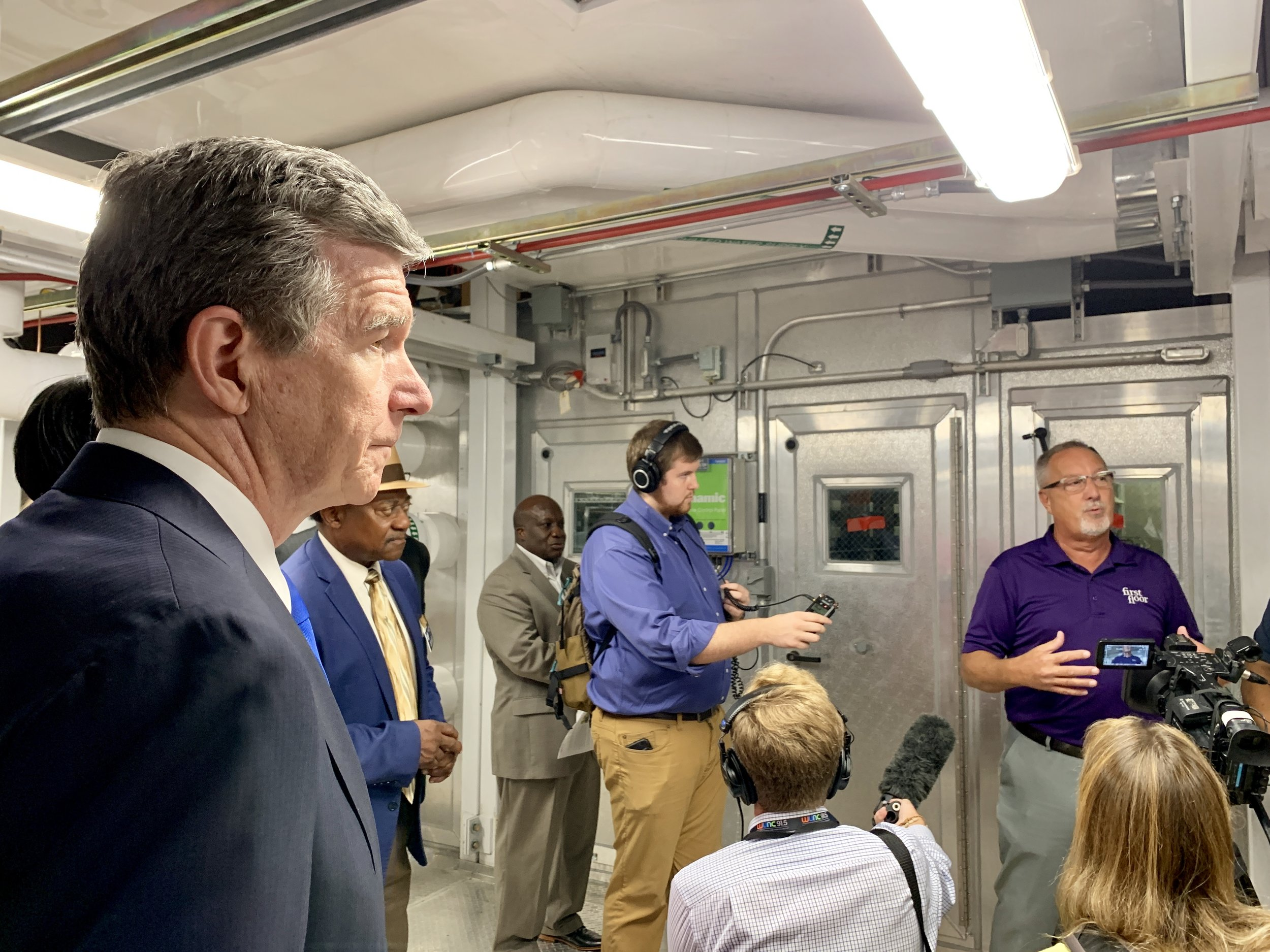 Gov. Roy Cooper listens to a description of some of the energy-saving systems built into the new school. Photo by Catherine Hardee / Neuse News