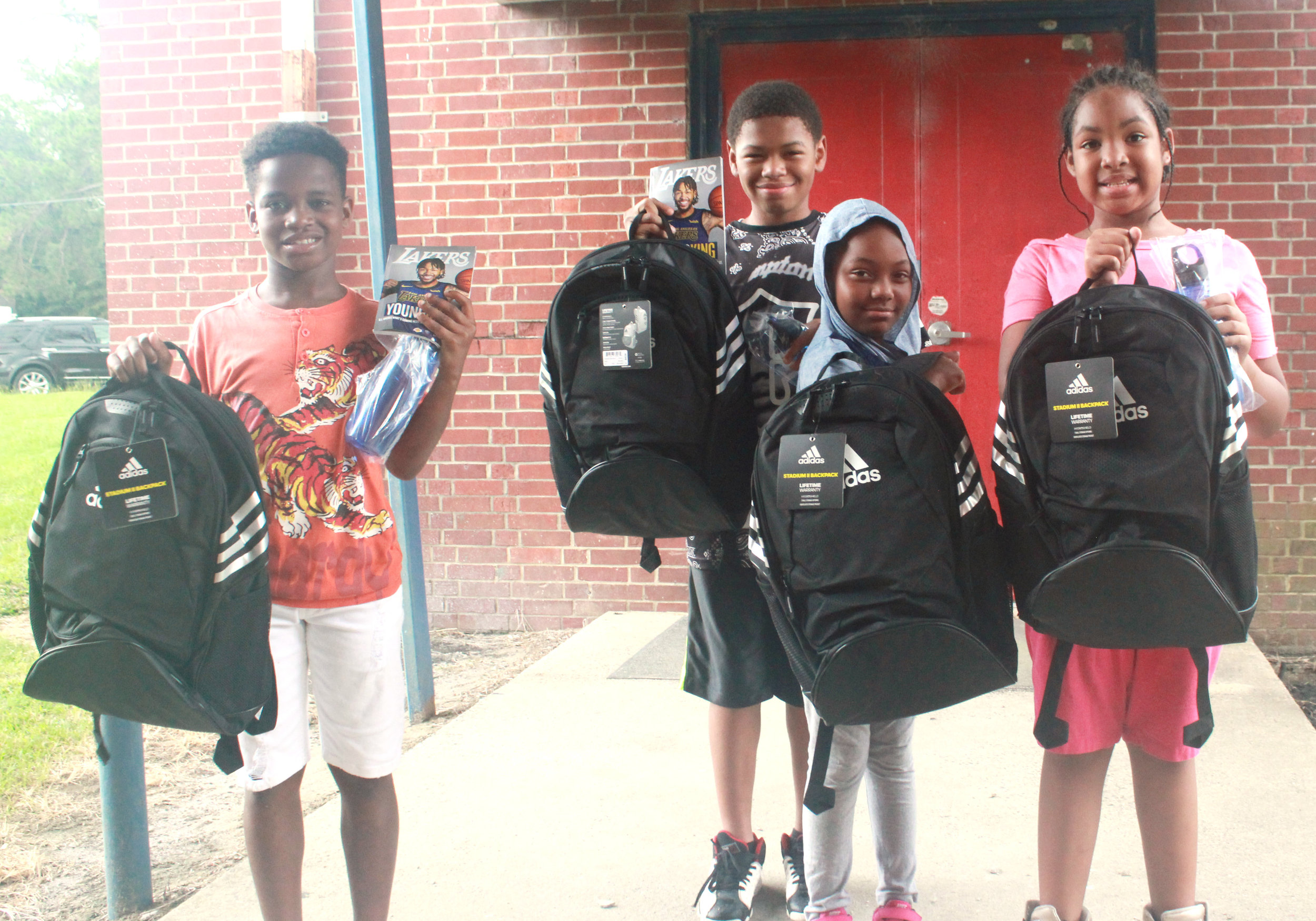 Four children show off the bookbags and school supplies they received from Brandon Ingram. Photo by Linda Whittington / Neuse News