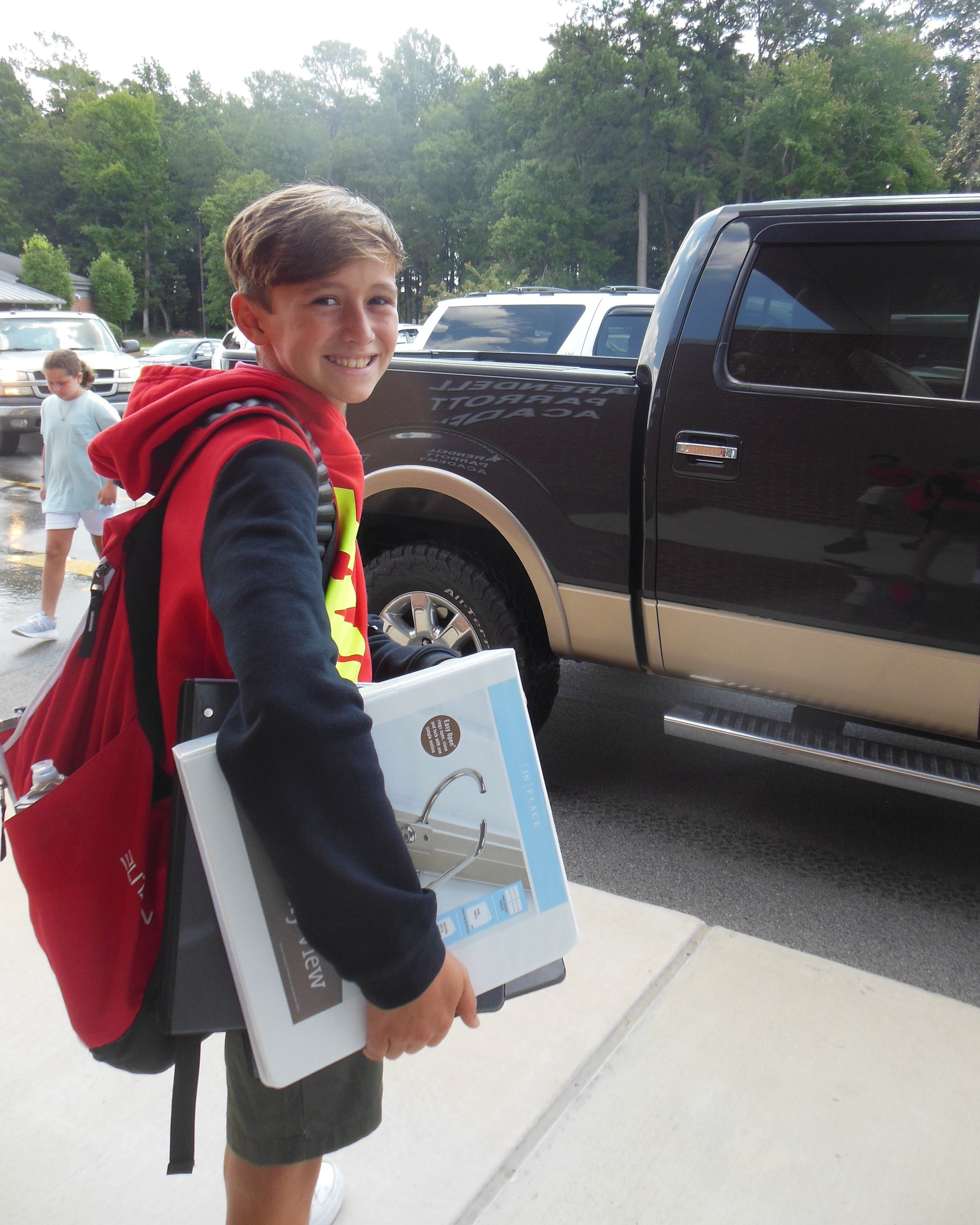 Ready to head home after his first day of middle school, 6th grader David Dunn waits to be picked up.