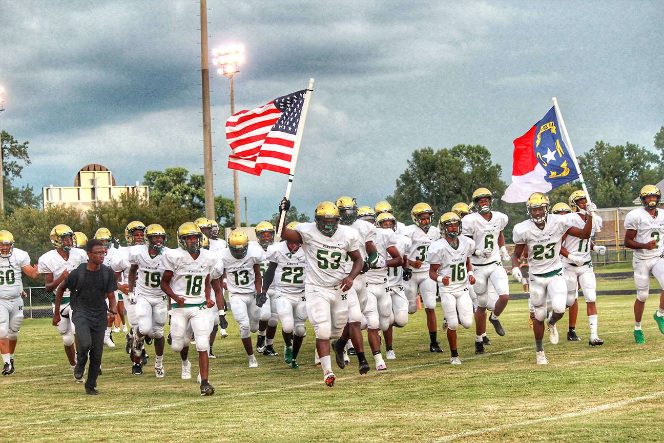 The Kinston Vikings, led by senior defensive lineman Walt Simmons (53) and senior receiver/defensive back Will London (23), run onto the field before Friday's season-opener at Farmville Central. Photo by Linda Whittington / Neuse News
