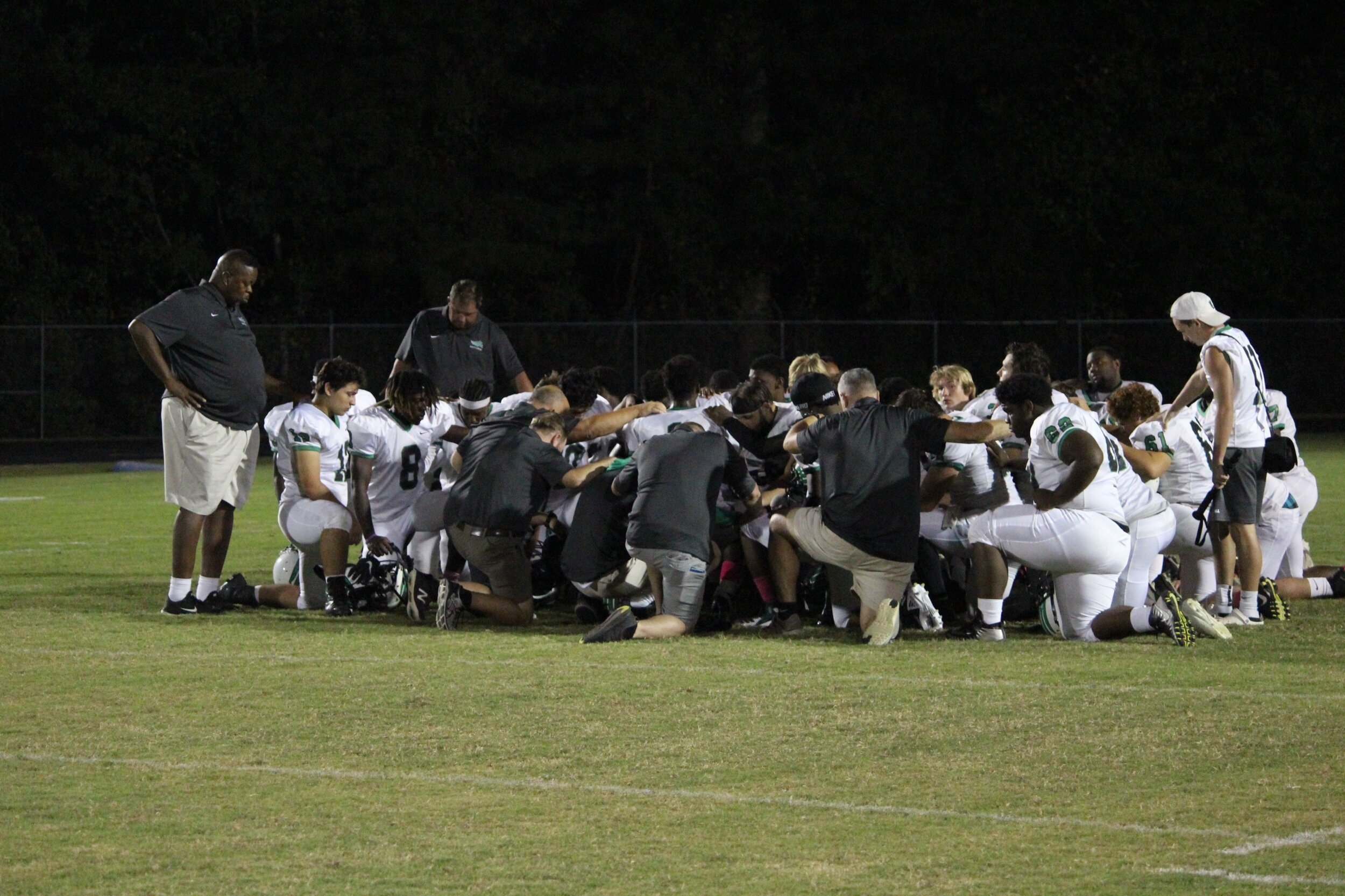 The North Lenoir Hawks football team says a postgame prayer after their 33-6 loss to Washington on Friday. Photo by Laieke Abebe / Neuse News