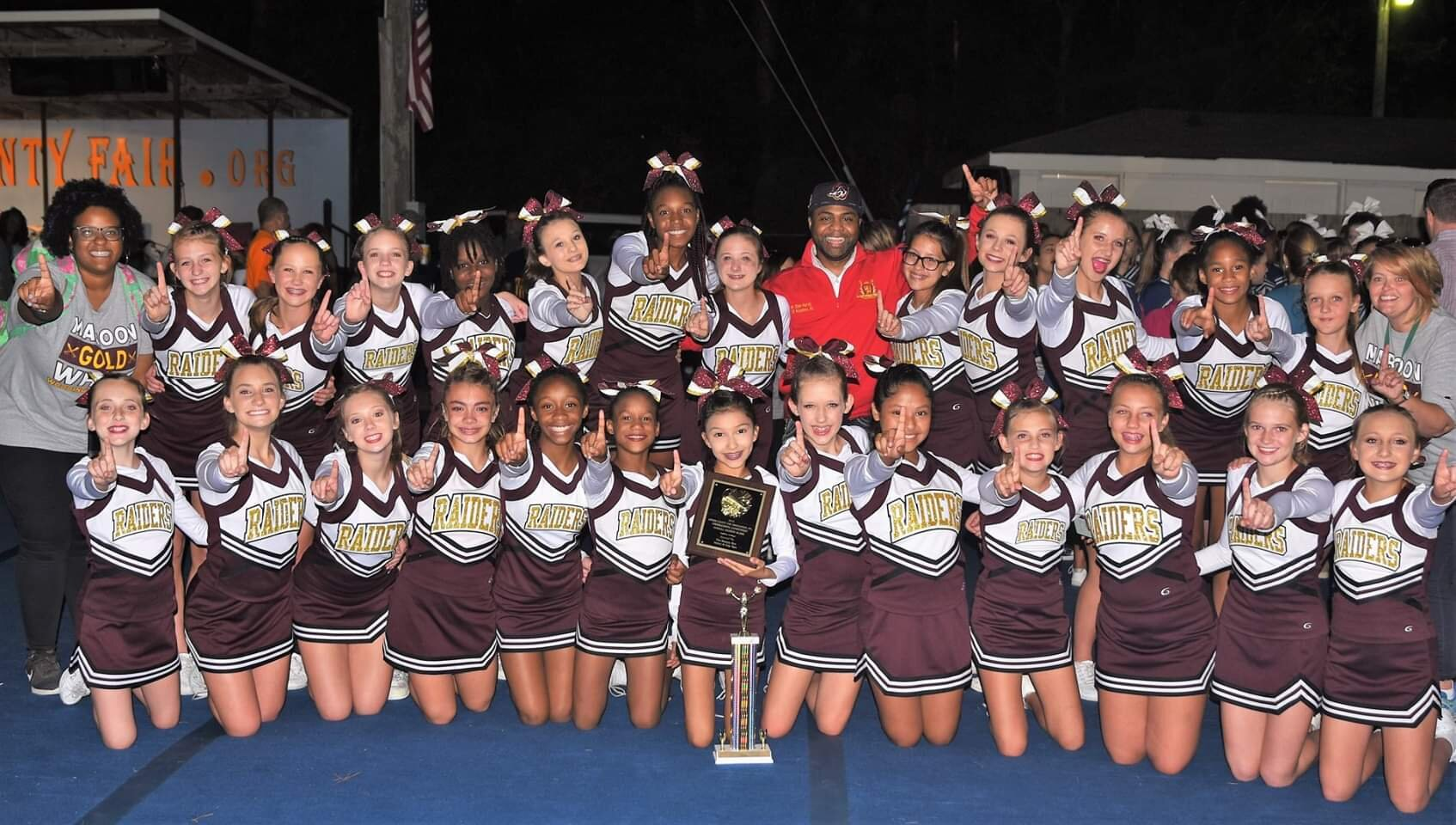 Woodington had the highest overall score in the 36th annual Lenoir County Agricultural Fair Cheerleading Competition on the way to the middle school crown. The Raiders celebrate their win with Kinston mayor Don Hardy. Photo by William 'Bud' Hardy / Neuse News