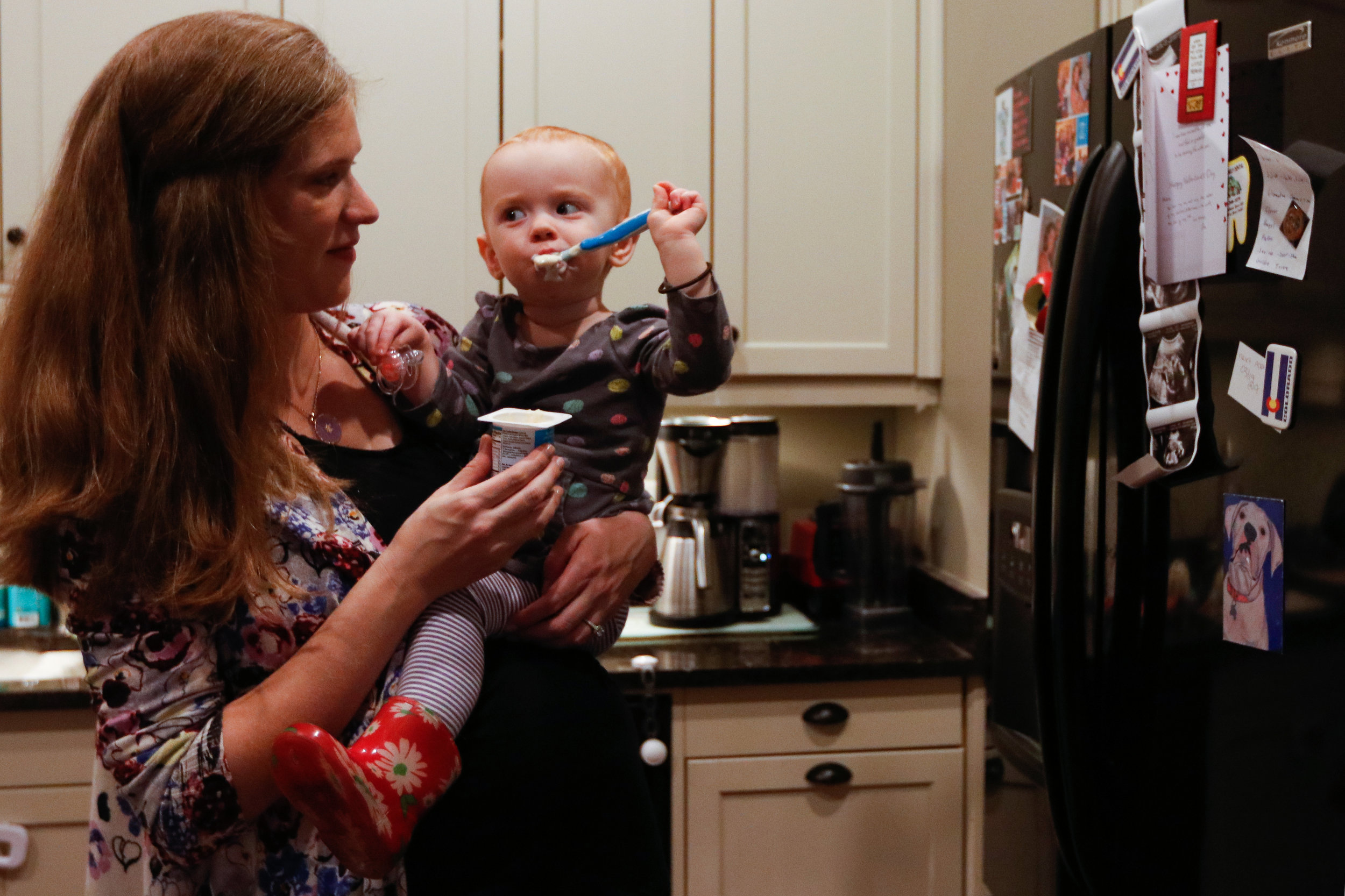 Juniper Zareie, 18 months, eats yogurt in her Athens, Georgia, home while mom Melanie stands by on March 19, 2018.