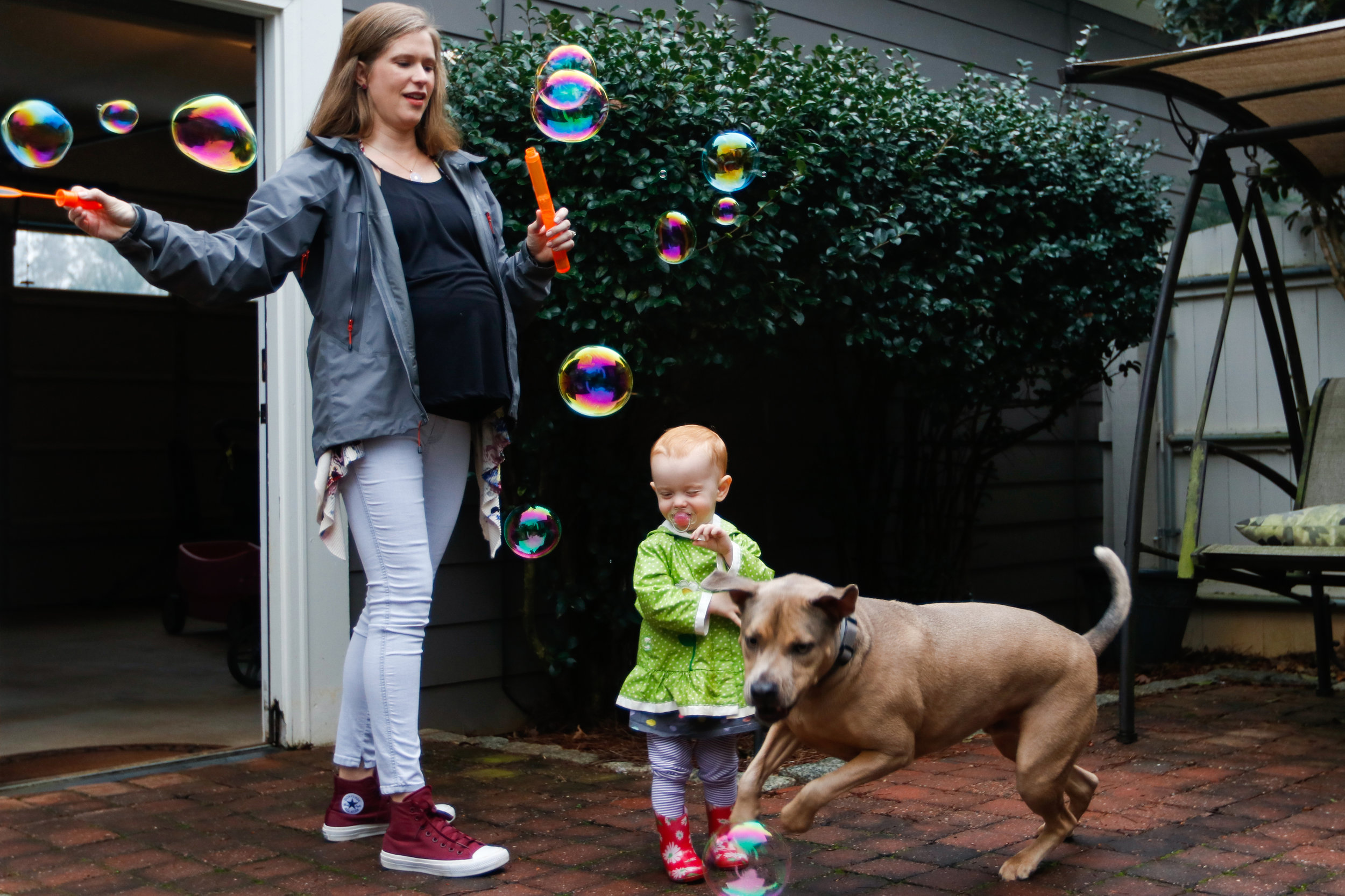 Melanie Zareie, 18-month-old daughter Juniper and dog Willy play with bubbles outside their Athens, Georgia, home on Monday, March 19, 2018.