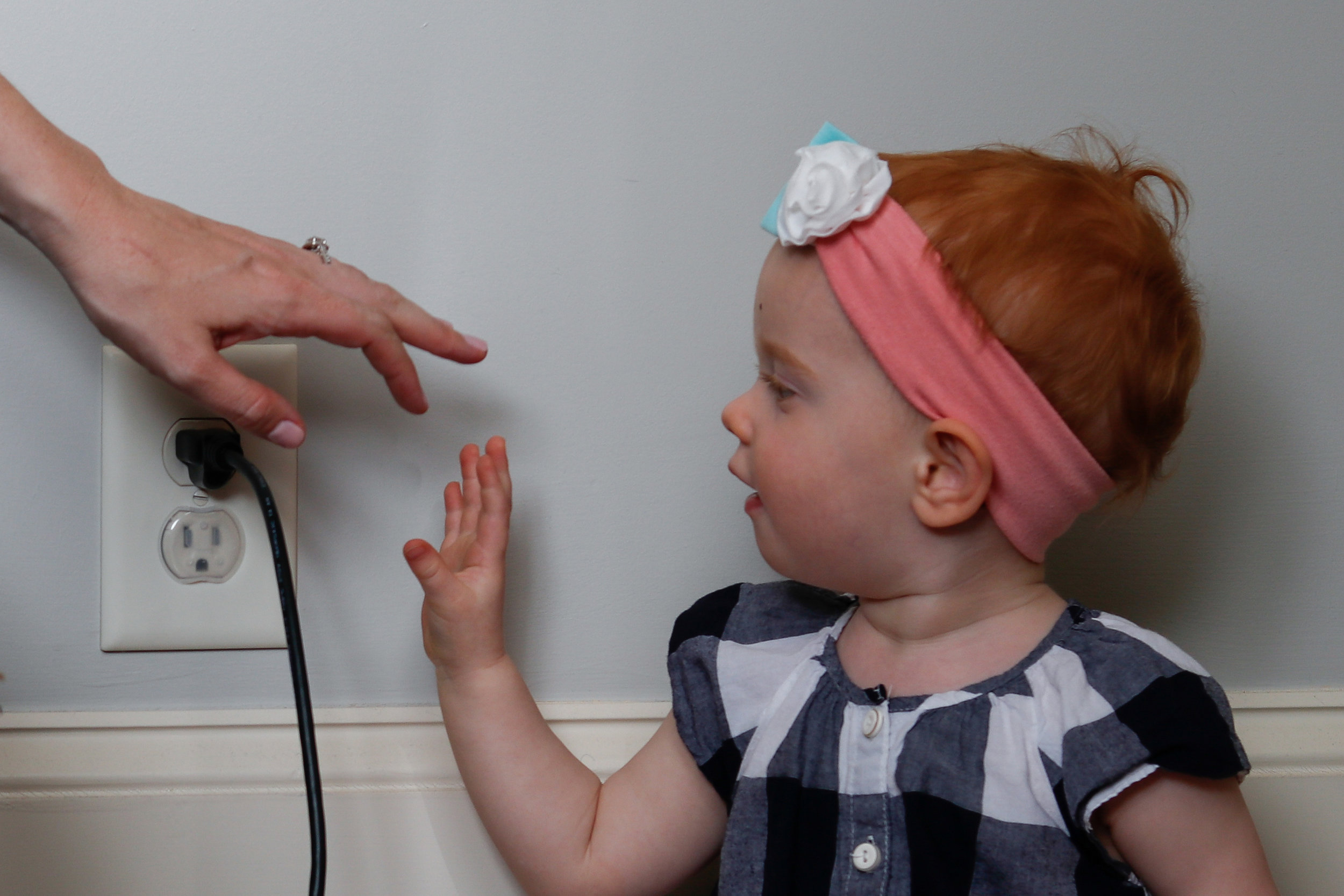 Melanie Zareie stops daughter, Juniper Zareie, 18 months, from touching an electrical outlet in their Athens, Georgia, home on Tuesday, April 3, 2018. Zareie is due to give birth to her second daughter, Olivia, in one week.
