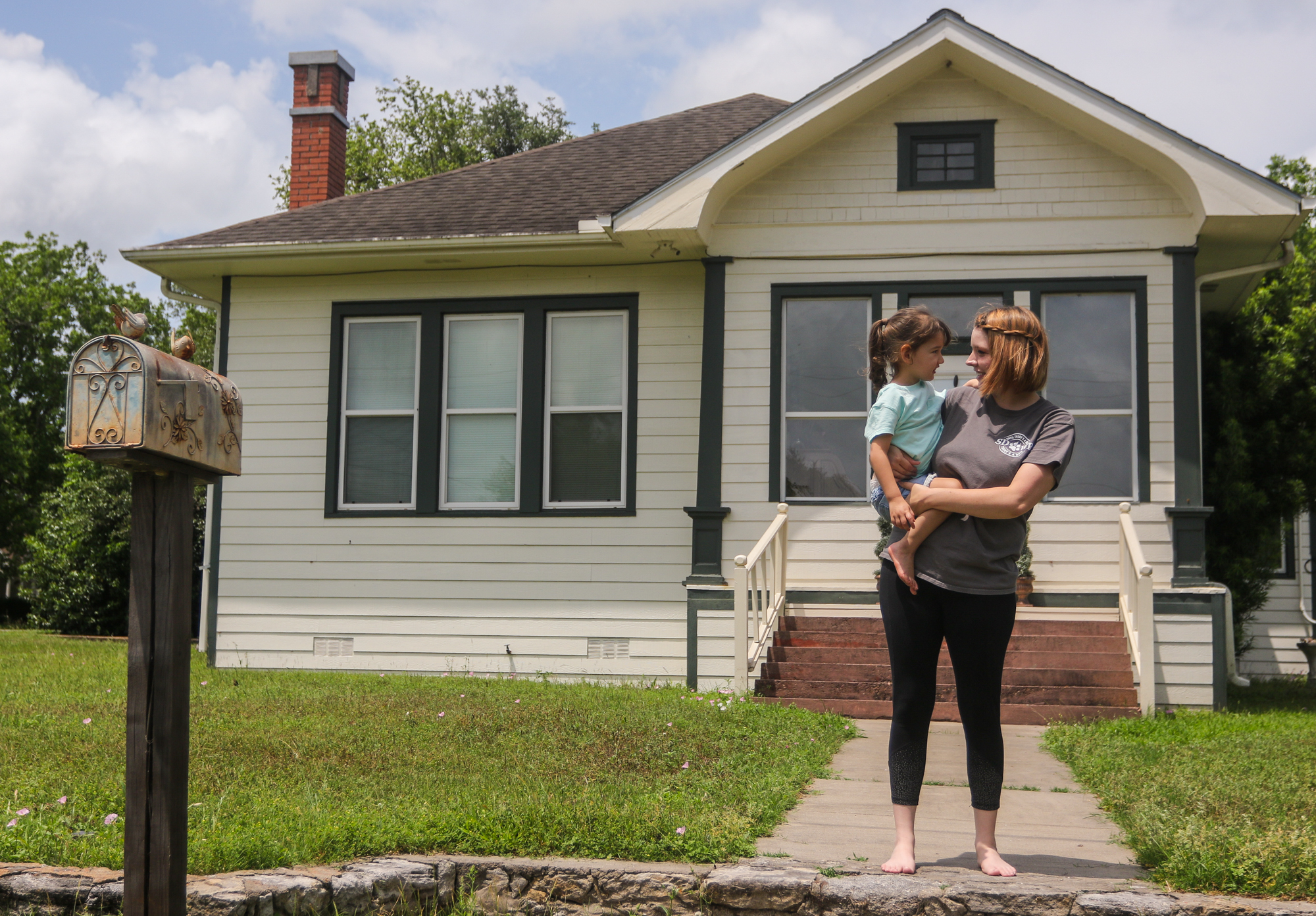 Brittany Cabrera, 25, holds her daughter Penny, 3, in front of their Goliad, Texas, home on May 2, 2019. The pair plans to permanently relocate to Colorado in June alongside Cabrera's husband and parents to seek medical marijuana treatments for Penny's seizures.