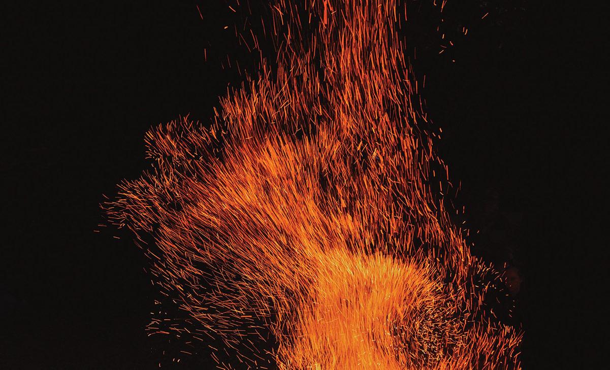 Orange fire sparks against a black background.