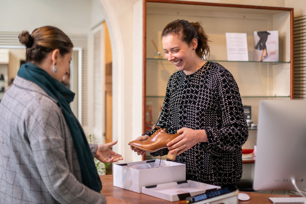 Dianne Sheehan giving shoe advice to a customer in her store, The House of Shoes. Image by Melanie de Ruyter 2019.