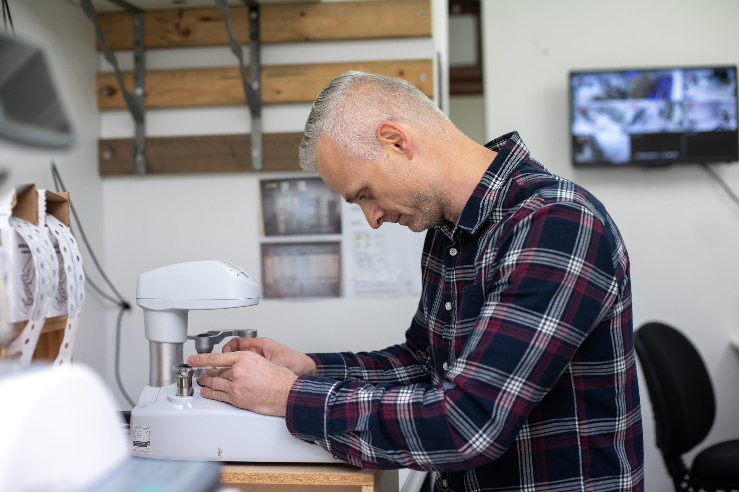 David Slama, part owner of  Reflekt  fits a customer's lenses into their chosen frame. Image: Melanie de Ruyter for Winterlicous 2019.